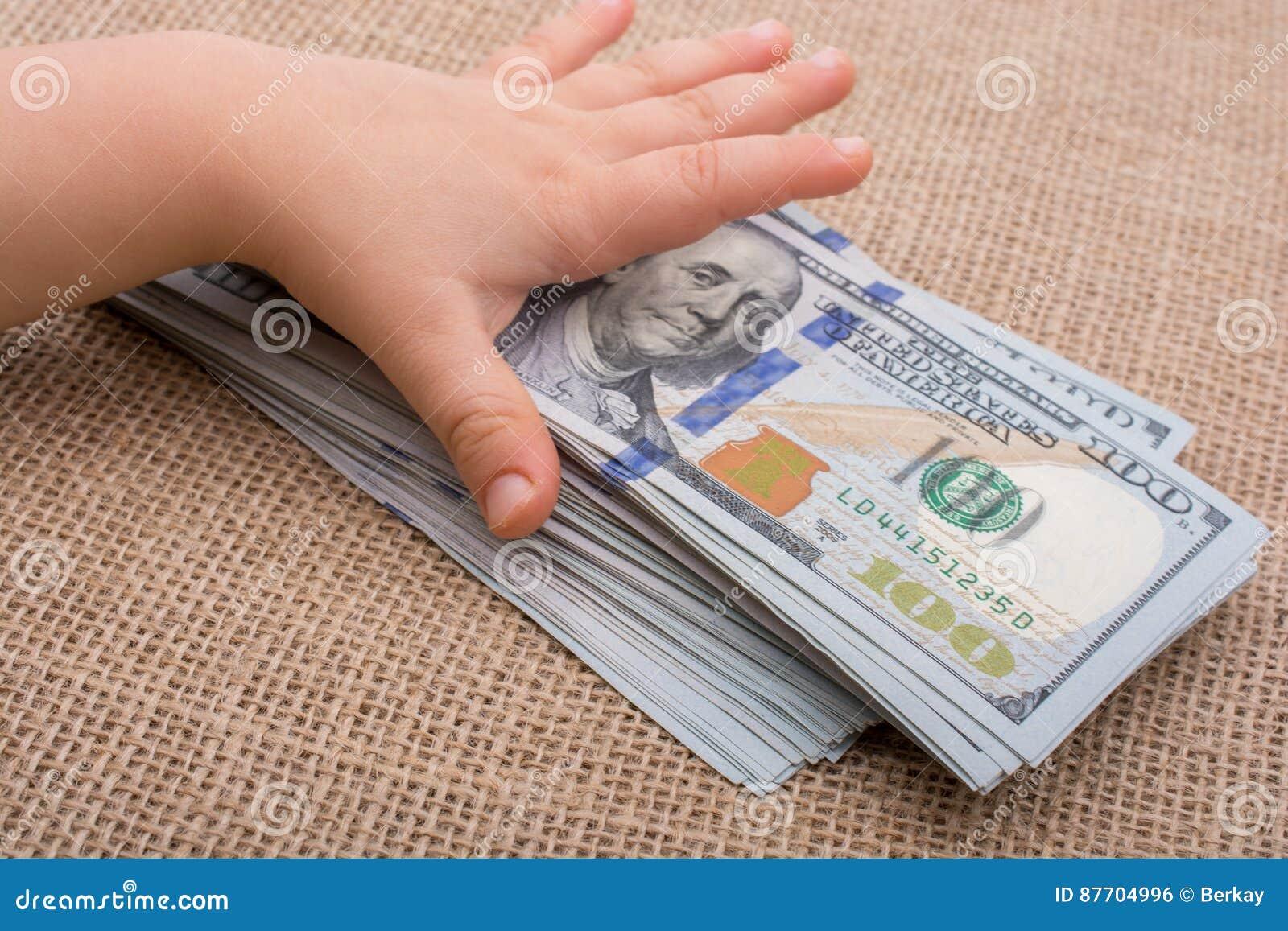 Main d enfant en bas âge jugeant le paquet de billet de banque du dollar US disponible