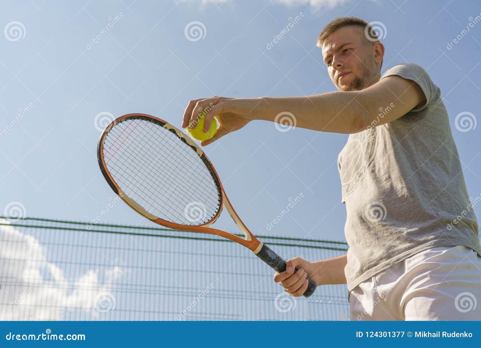 Main d homme de joueur de tennis faisant un tir tenant une boule et une raquette contre le ciel