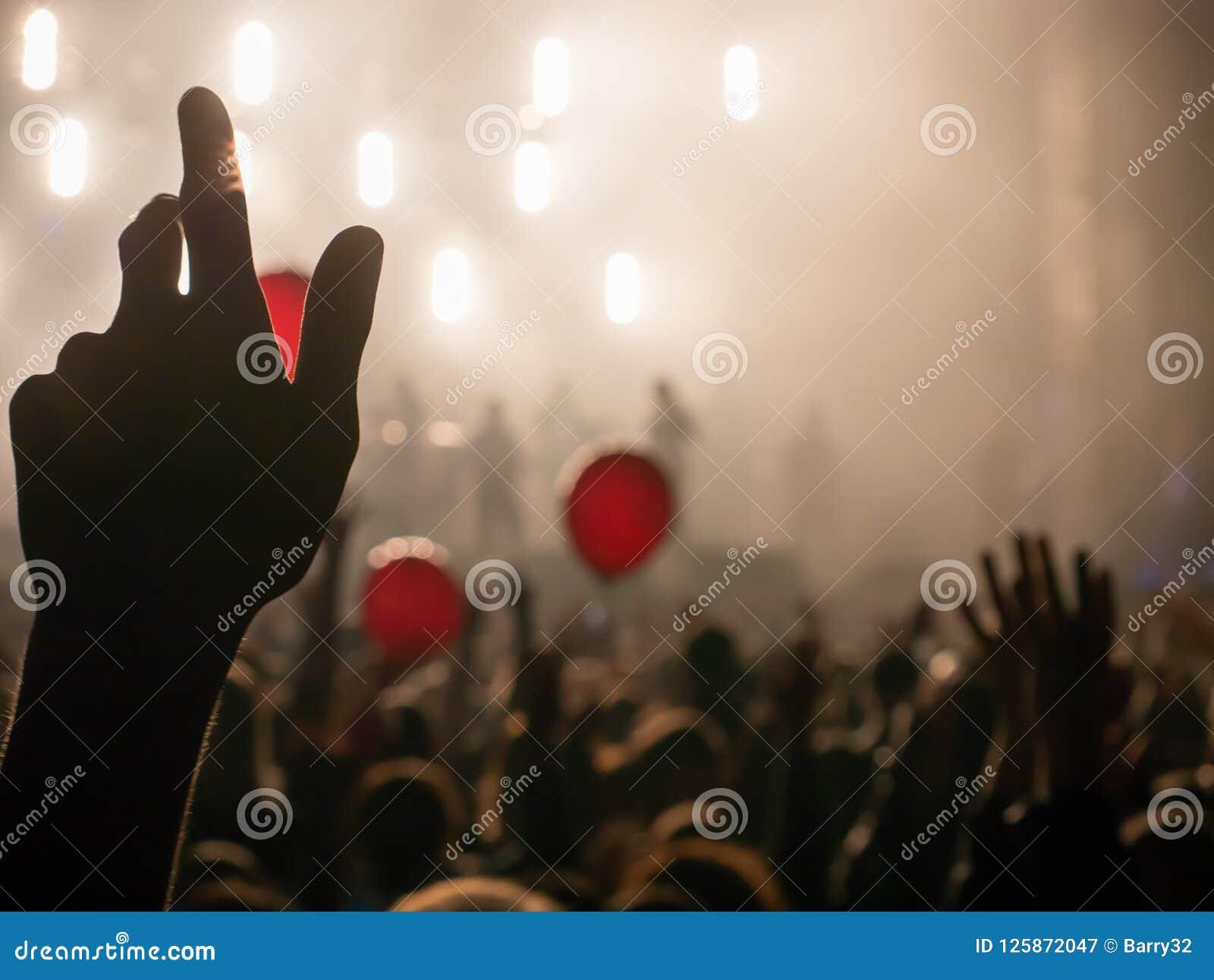 Main dans le ciel pendant le concert de rock silhouetté contre les lumières lumineuses