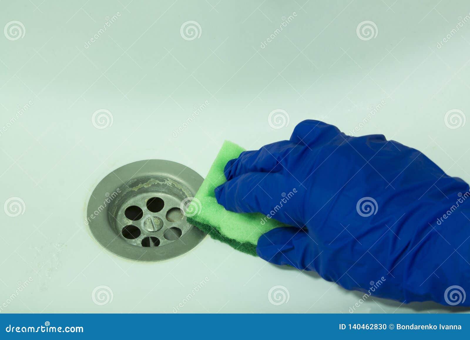 Main dans les gants bleus de sécurité avec une éponge nettoyant un évier de bain