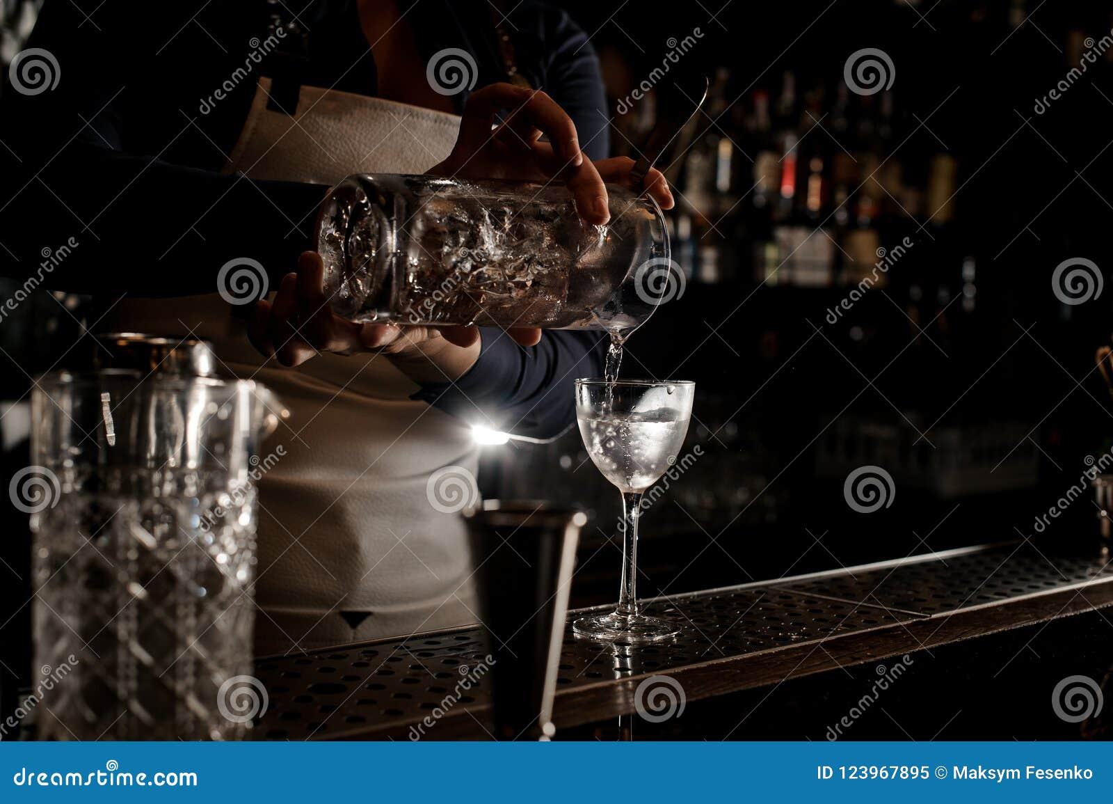 Main de barmaid versant le cocktail frais dans un verre