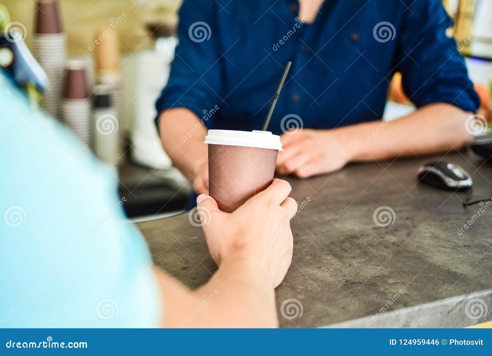 Main de barman au café de service de barre pour le client La main donne la tasse au visiteur de client Appréciez votre boisson L