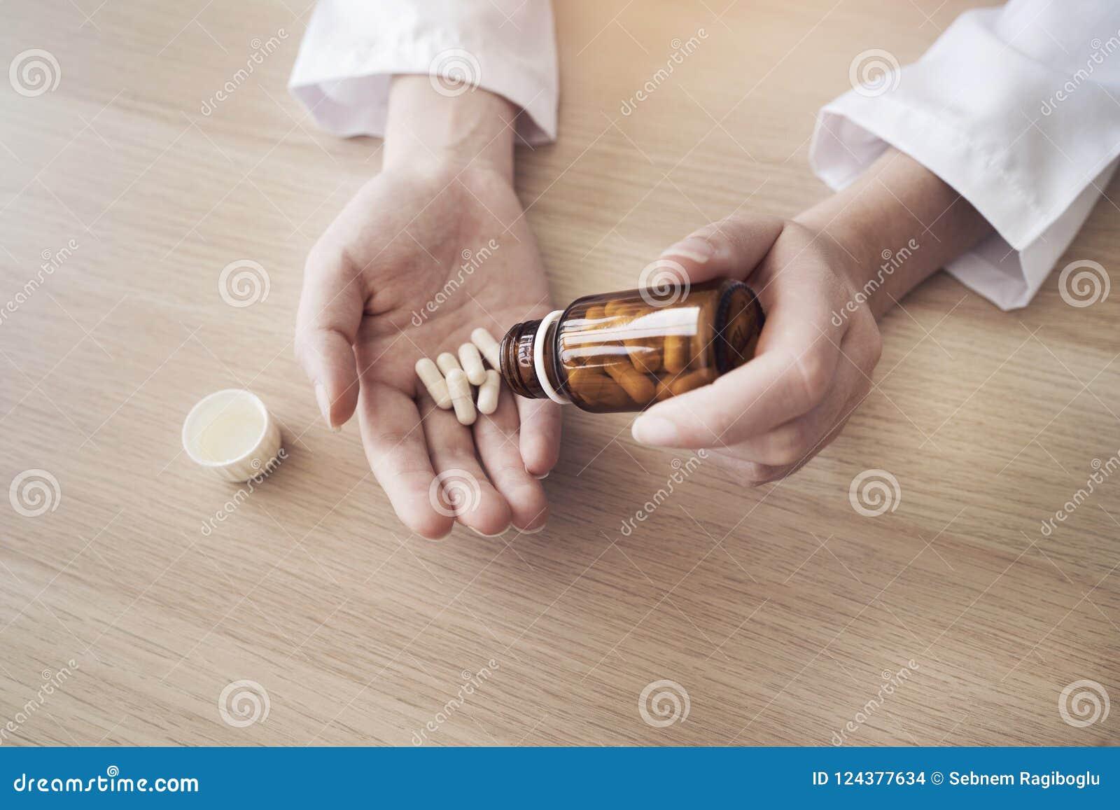Main de docteur féminin tenant des pilules