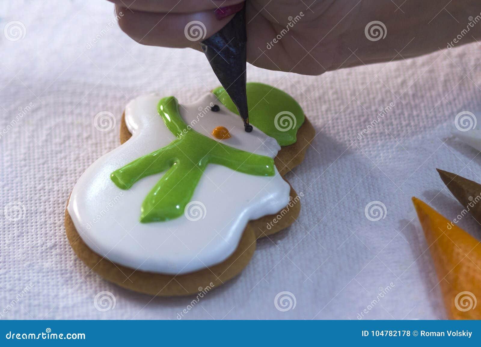 Main de femme décorant le pain d épice sous forme d un bonhomme de neige avec du sucre glace utilisant un sac pipping Festins de
