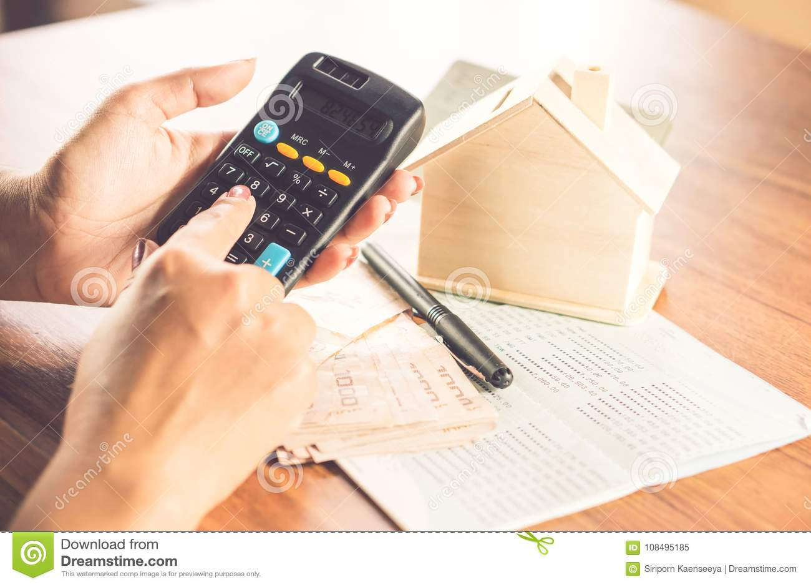 Main de femme d affaires comptant la devise de papier d argent avec le livre de comptes d économie, le modèle de maison et la cal