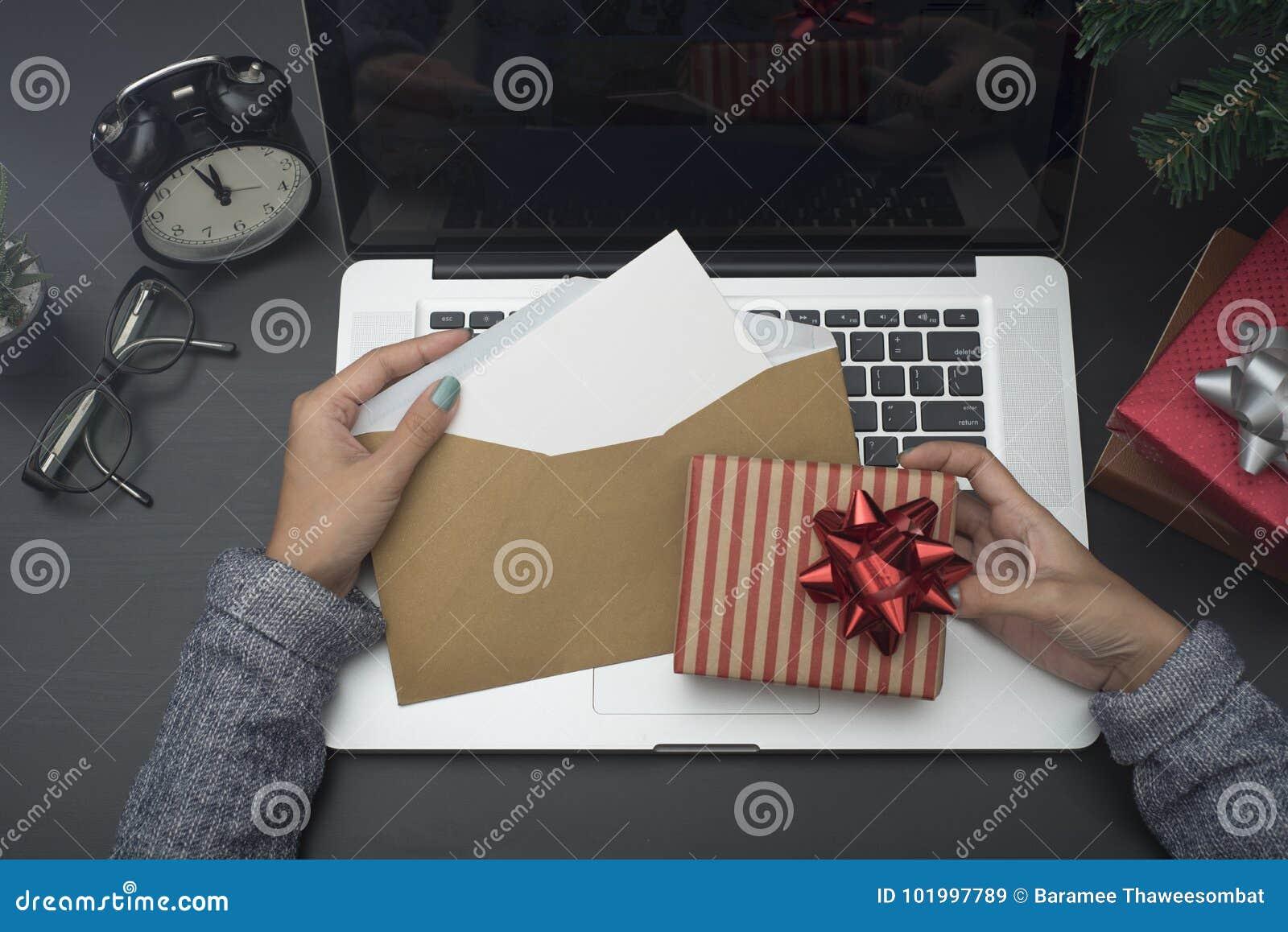 Main de femme daffaires tenant la carte et le boîte cadeau de noël
