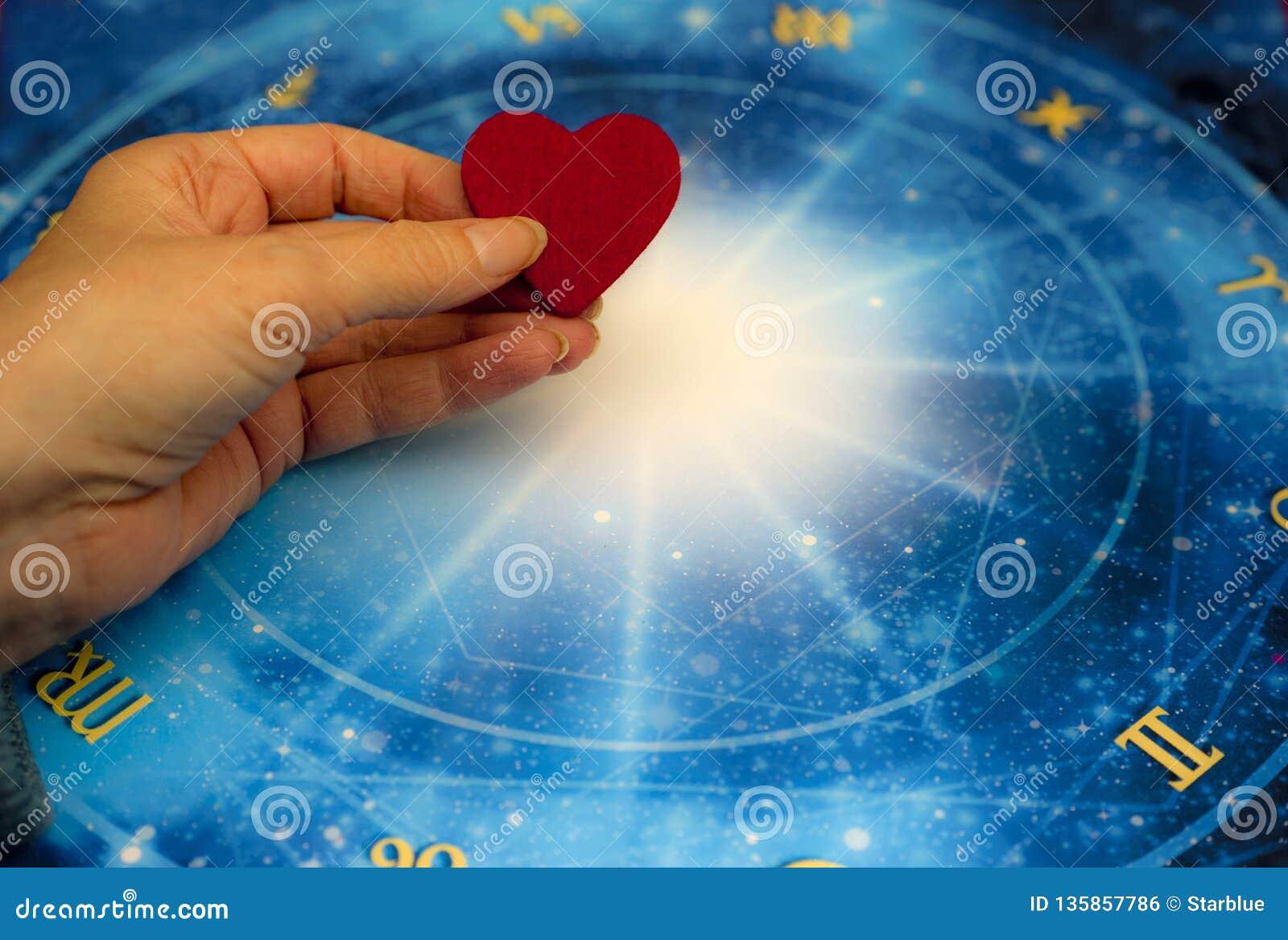 Main de femme gardant un coeur rouge au-dessus d horoscope bleu comme le concept d astrologie, de zodiaque et d amour