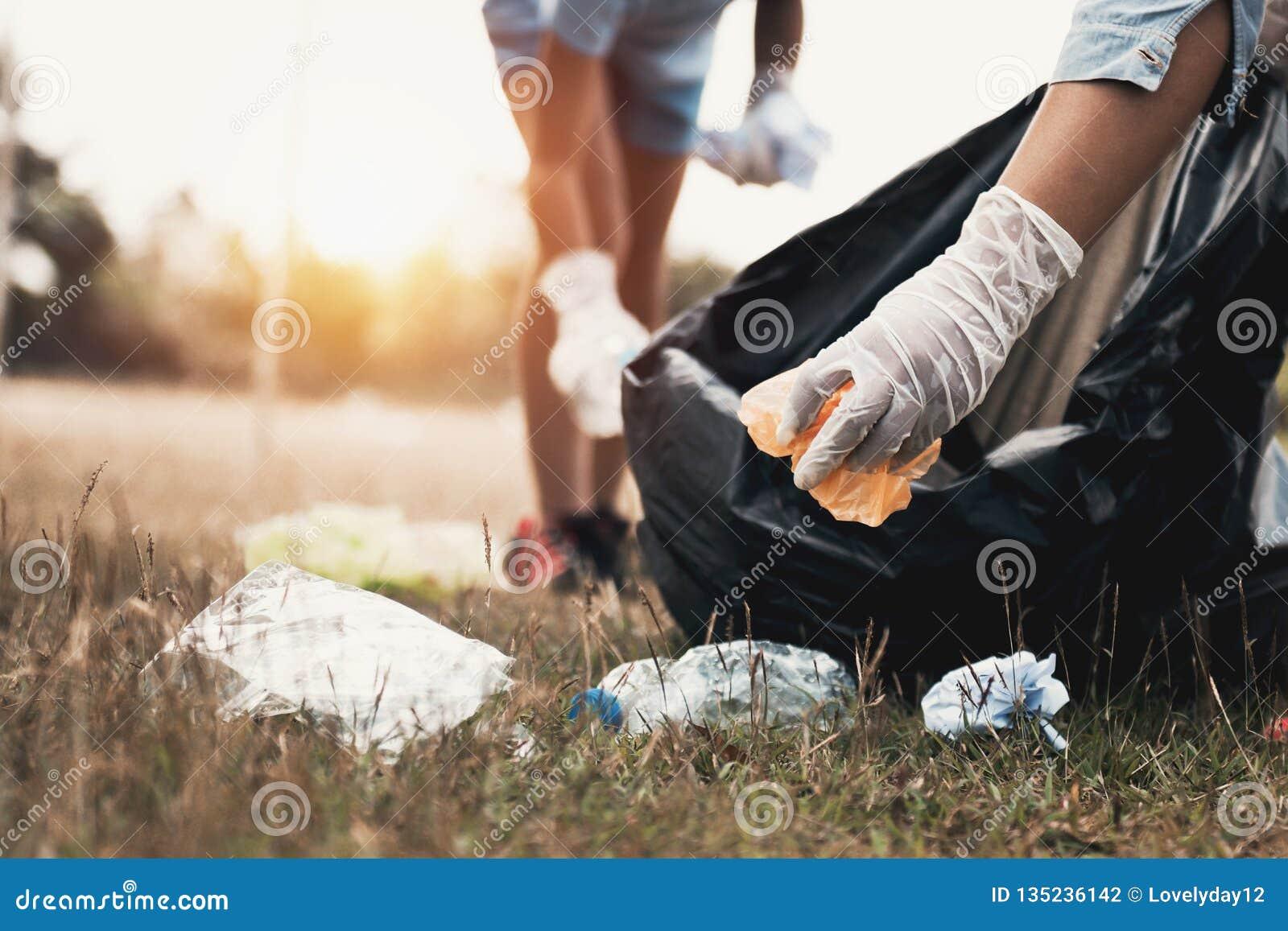Main de femme prenant le plastique de déchets pour le nettoyage