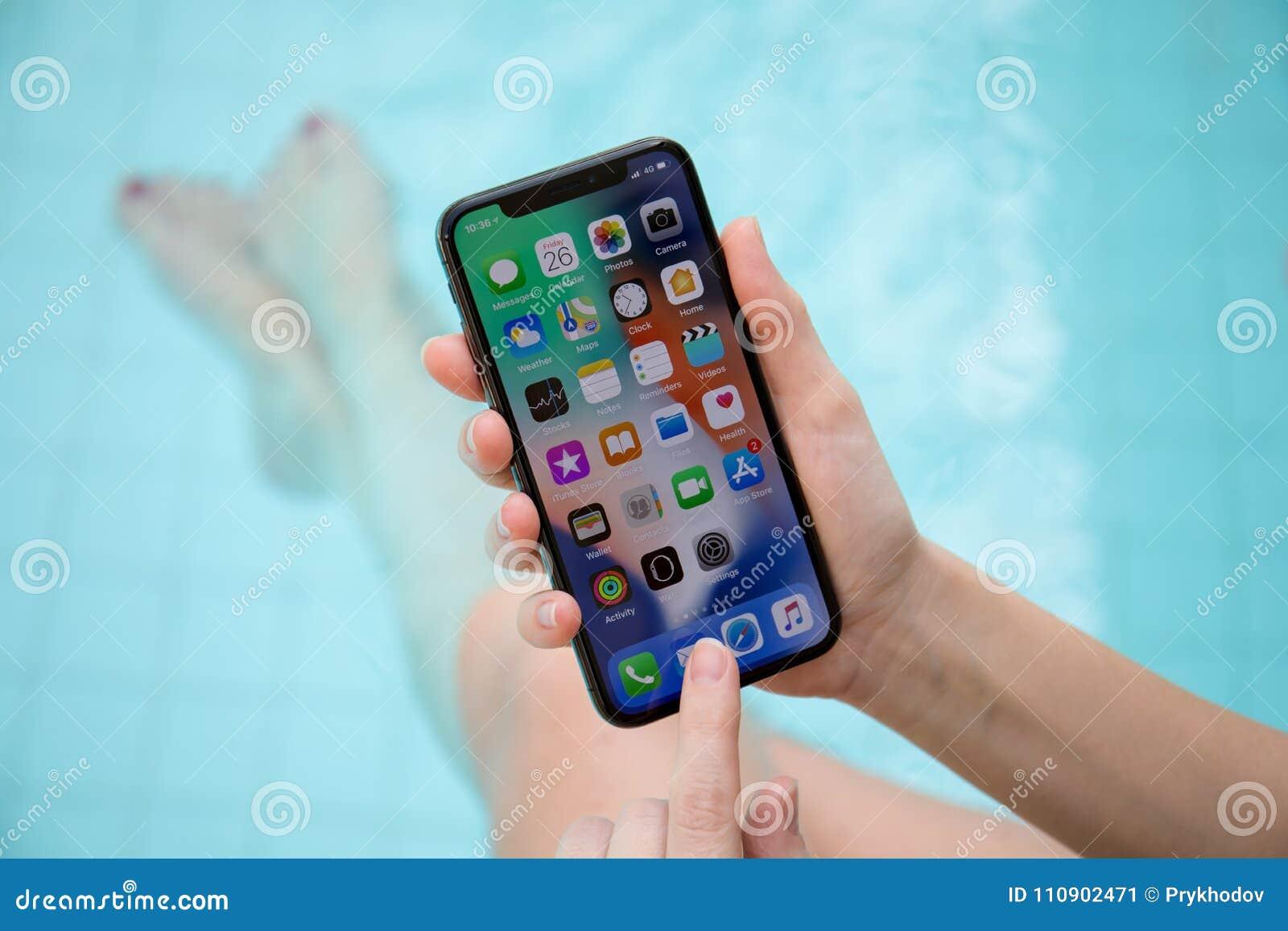 Main de femme tenant l iPhone X avec IOS 11 sur l écran
