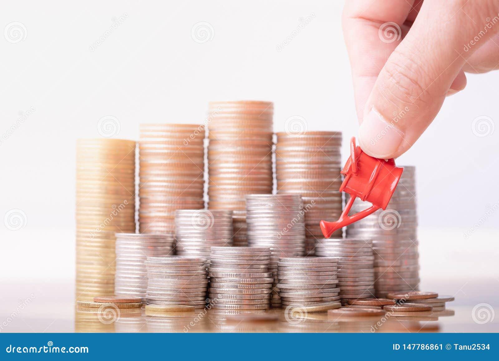 Main de femme tenant la boîte d arrosage rouge sur la pile d argent