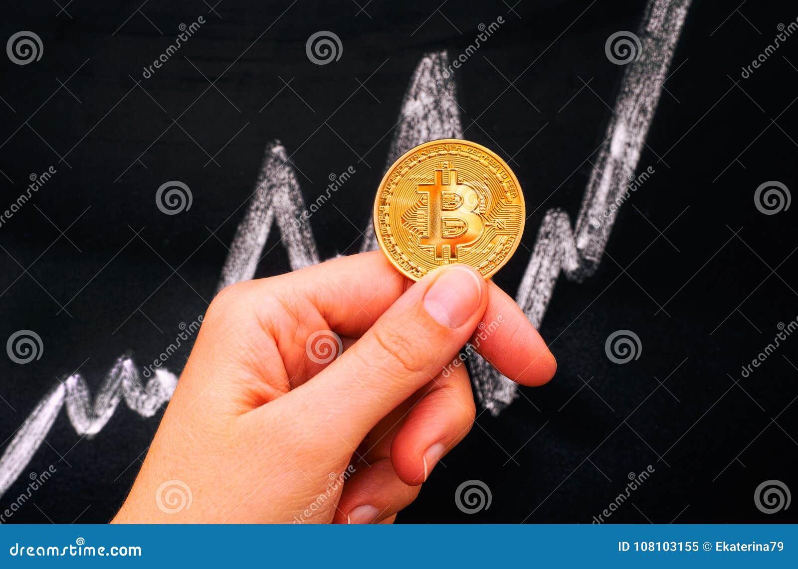 Main de femme tenant la pièce de monnaie virtuelle d or de Bitcoin contre blackboar