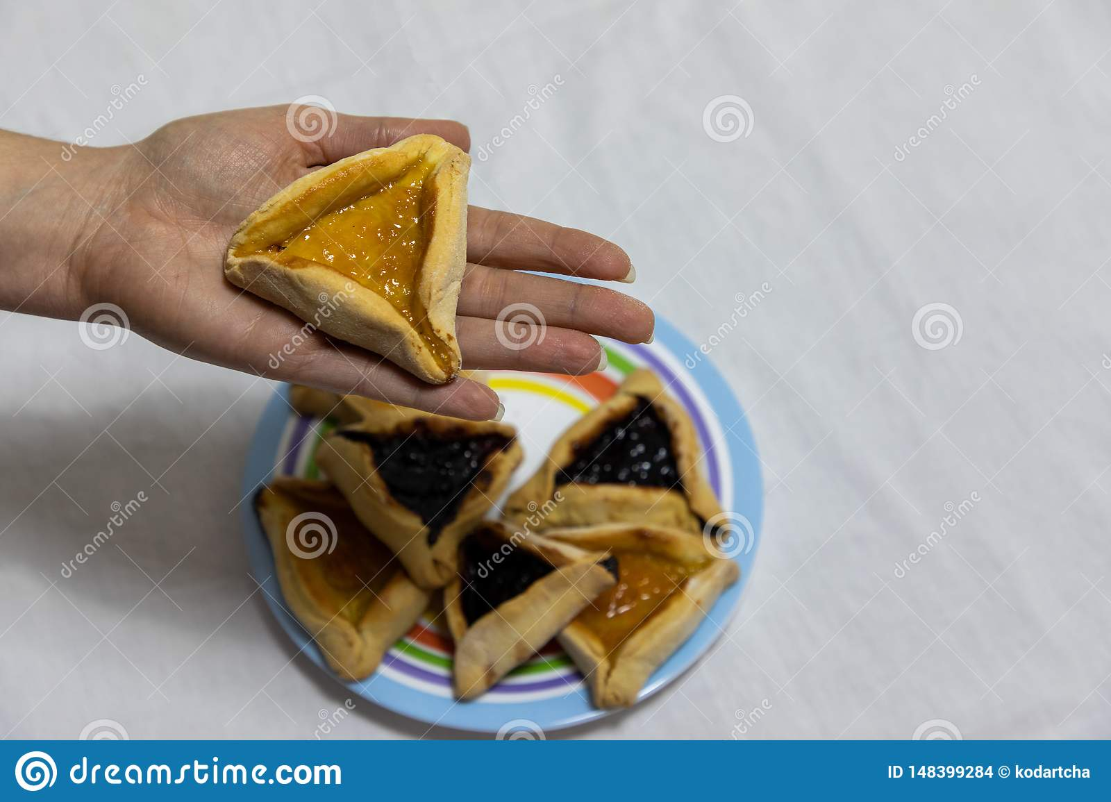 Main de femme tenant le biscuit de hamantash sur le plat color? avec plus de biscuits de hamantash