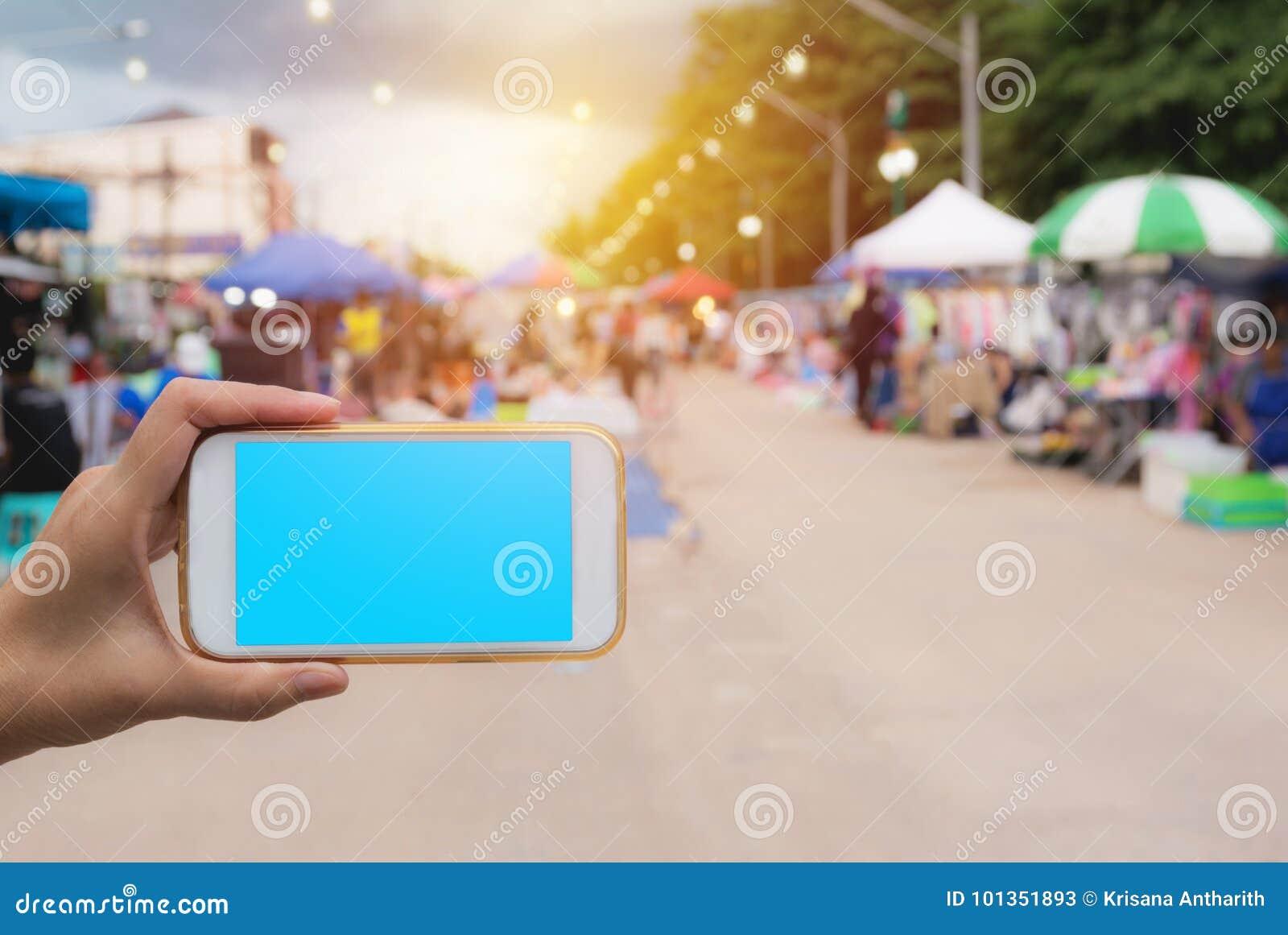 Main de femme tenant le téléphone intelligent dans la tache floue d achats de marché en plein air