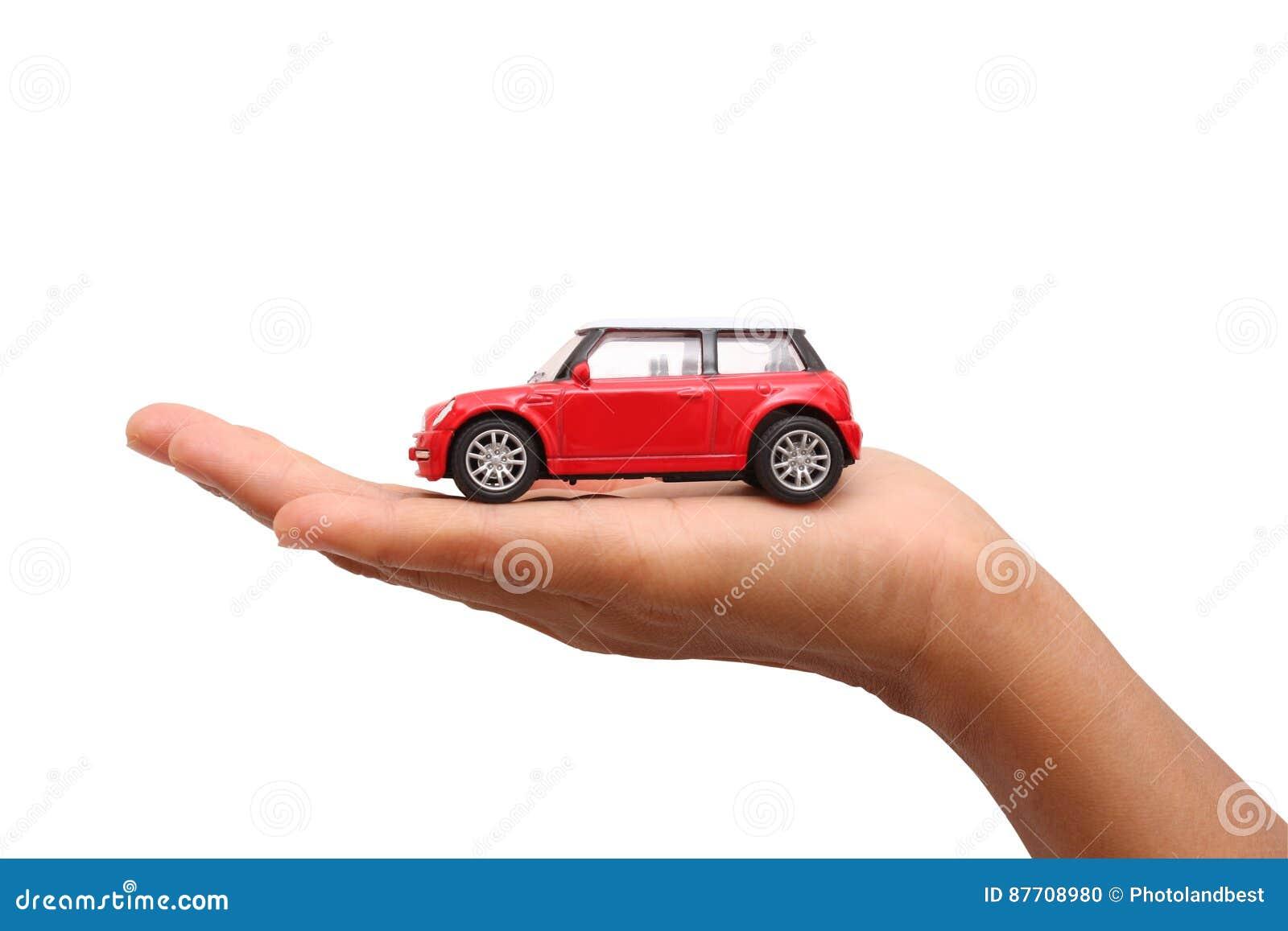 Main de femme tenant une voiture rouge de jouet