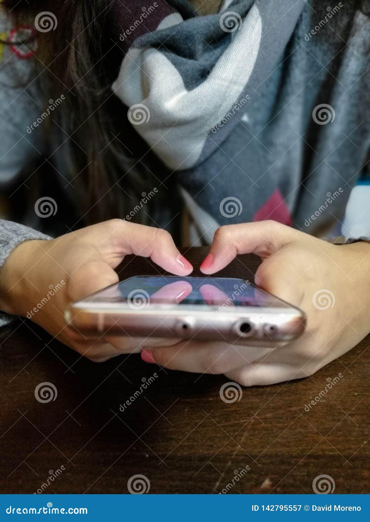 Main de femme utilisant le smartphone au cafétéria Jeune femelle utilisant le téléphone intelligent au restaurant
