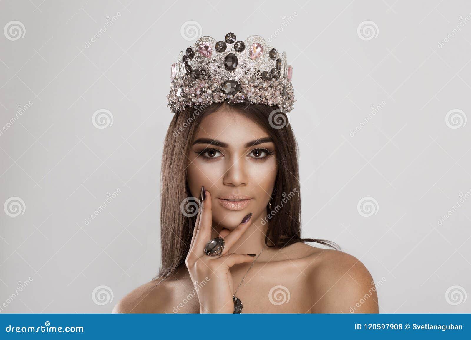 Main de jeune mariée de coup manqué de femme de fille de reine couronnée par beauté sur le menton