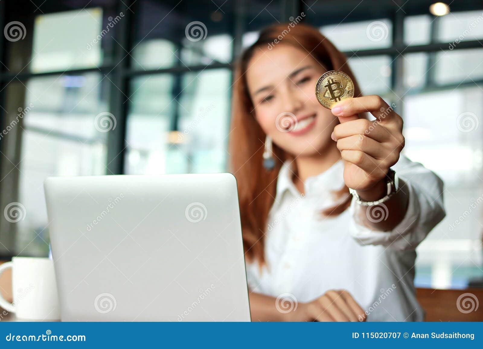 Main de la femme asiatique d affaires montrant à cryptocurrency la pièce de monnaie d or de bitcoin dans le bureau Argent virtuel