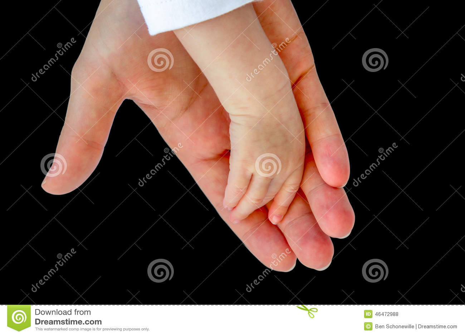 Main de mère tenant le bras du bébé sur le noir