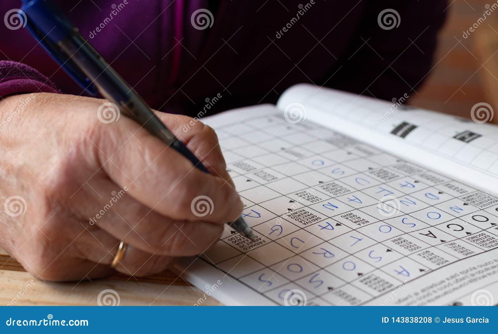 Main de personne supérieure faisant le jeu de mots croisé dans un carnet Loisirs et temps libre