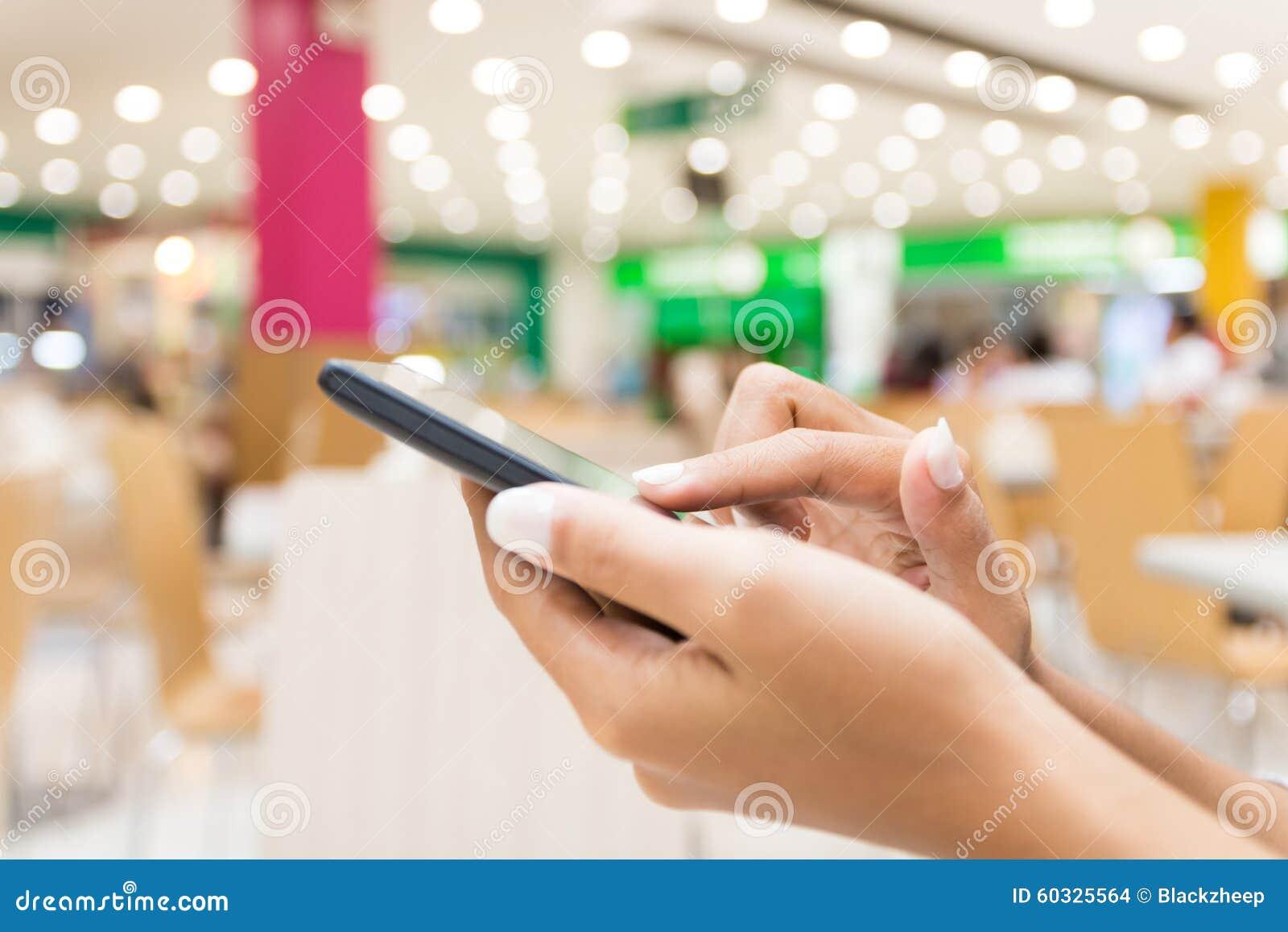 photo stock main de plan rapprochCA utilisant le tCAlCAphone intelligent dans lifesty urbain magasin image