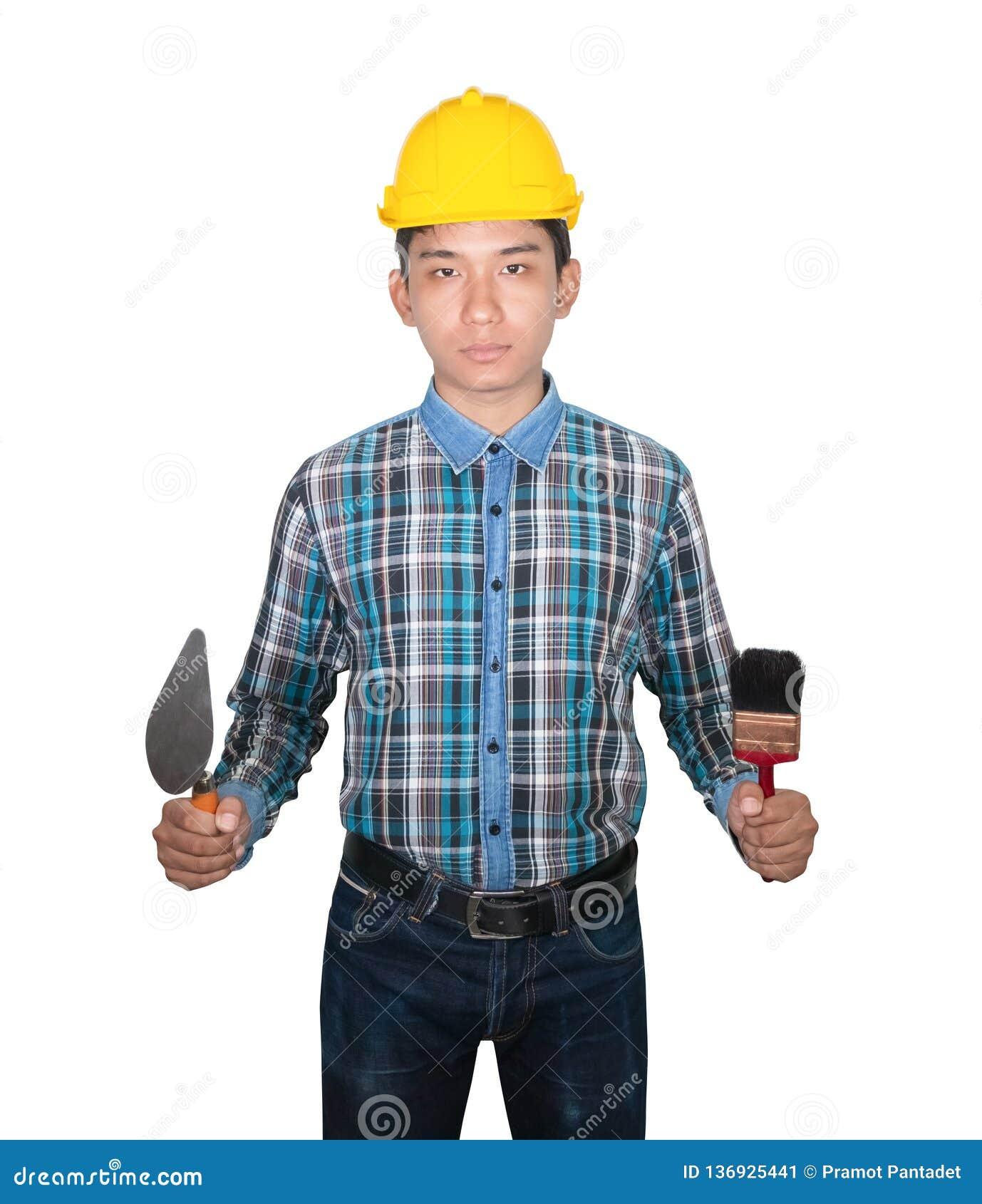 Main de plastique jaune de casque de sécurité d usage de pinceau de truelle et de triangle de participation d ingénieur sur le fo