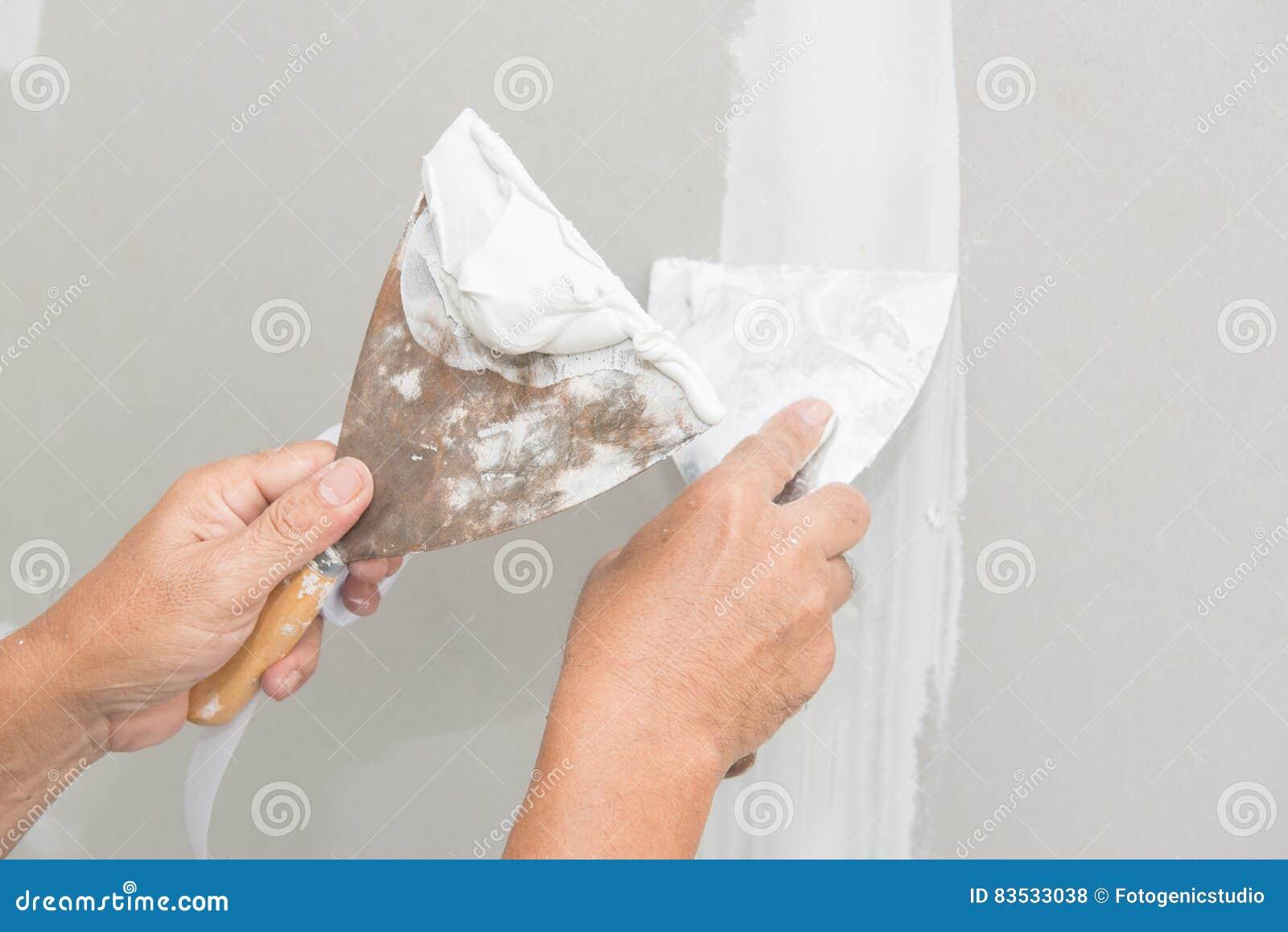 Main de travailleur avec le plâtre et la truelle au panneau de gypse