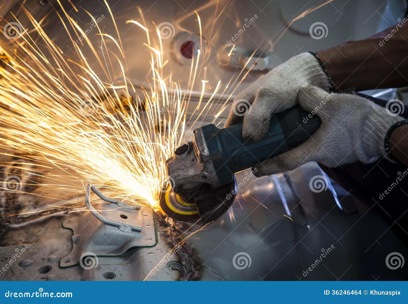 Main de travailleur fonctionnant à côté de l outil d industrie coupant l acier avec la fente fi