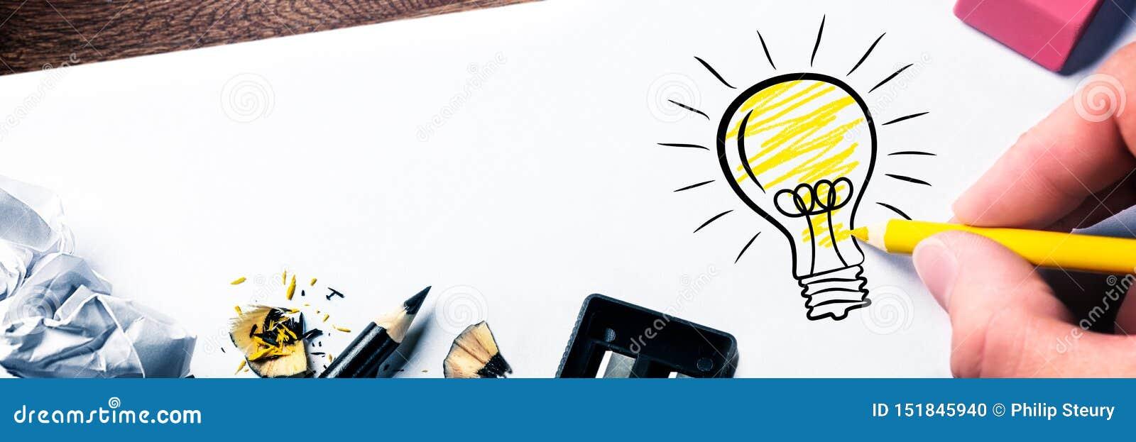 Main dessinant l ampoule sur le papier