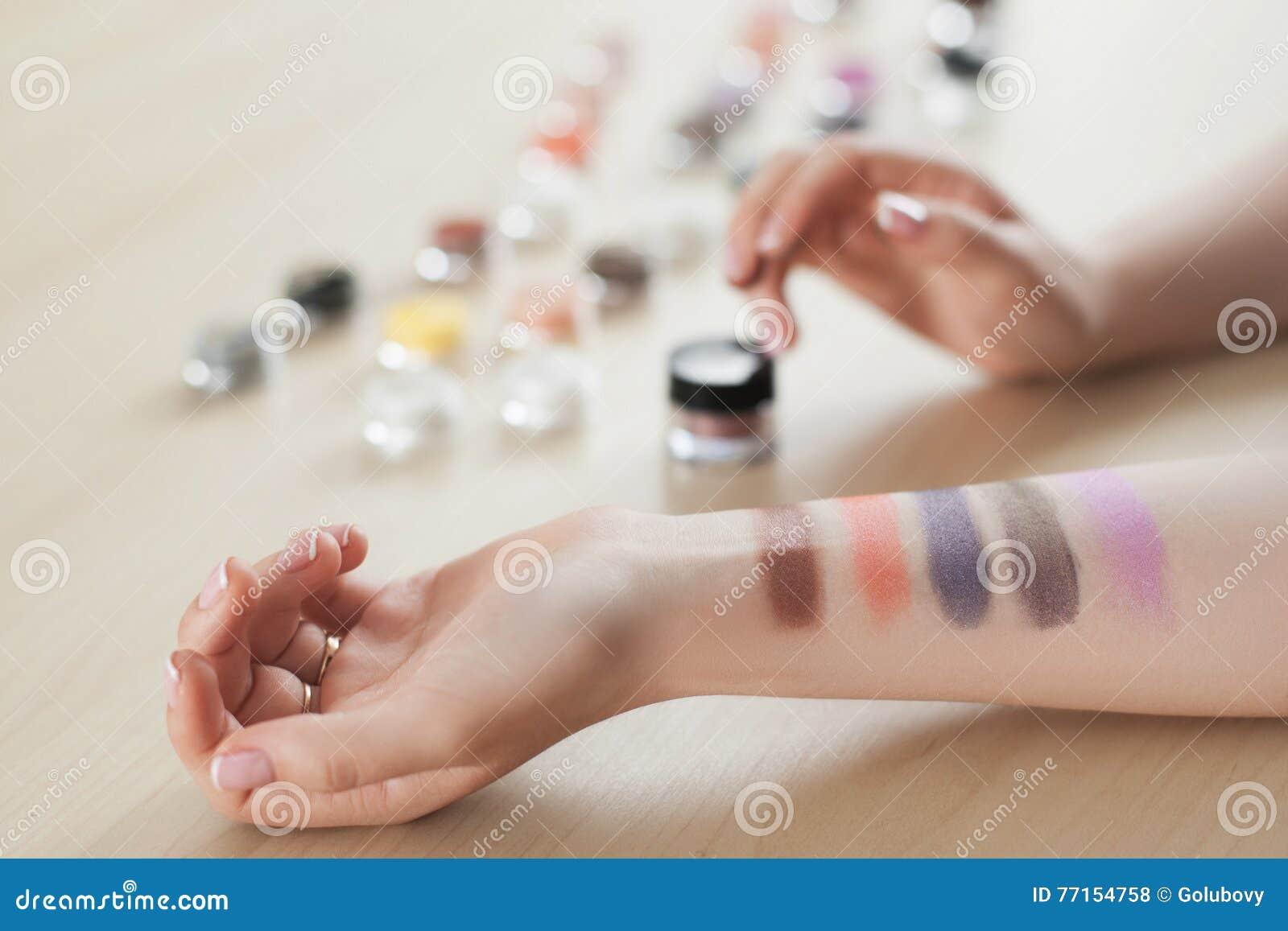 Main femelle avec des couleurs de fard à paupières, plan rapproché
