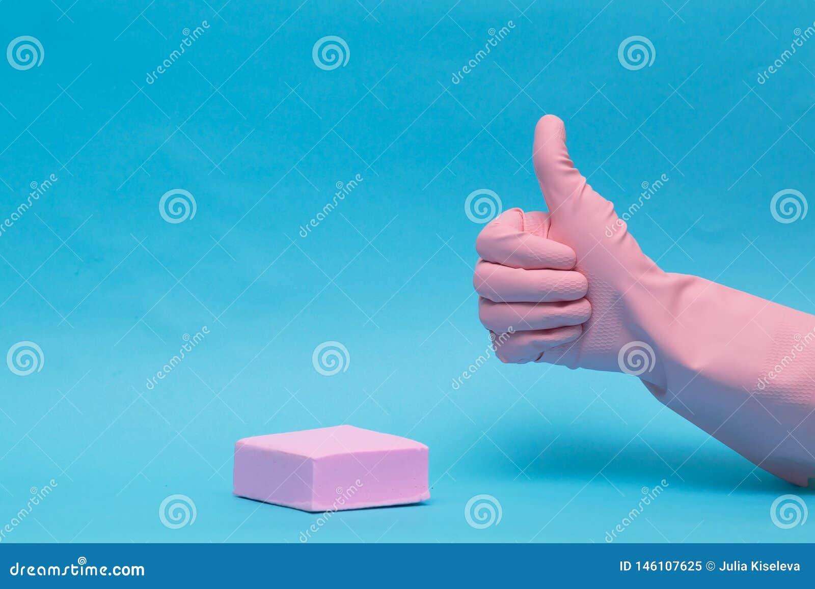 Main femelle dans le gant en caoutchouc rose, avec augmenté le doigt sur le fond bleu