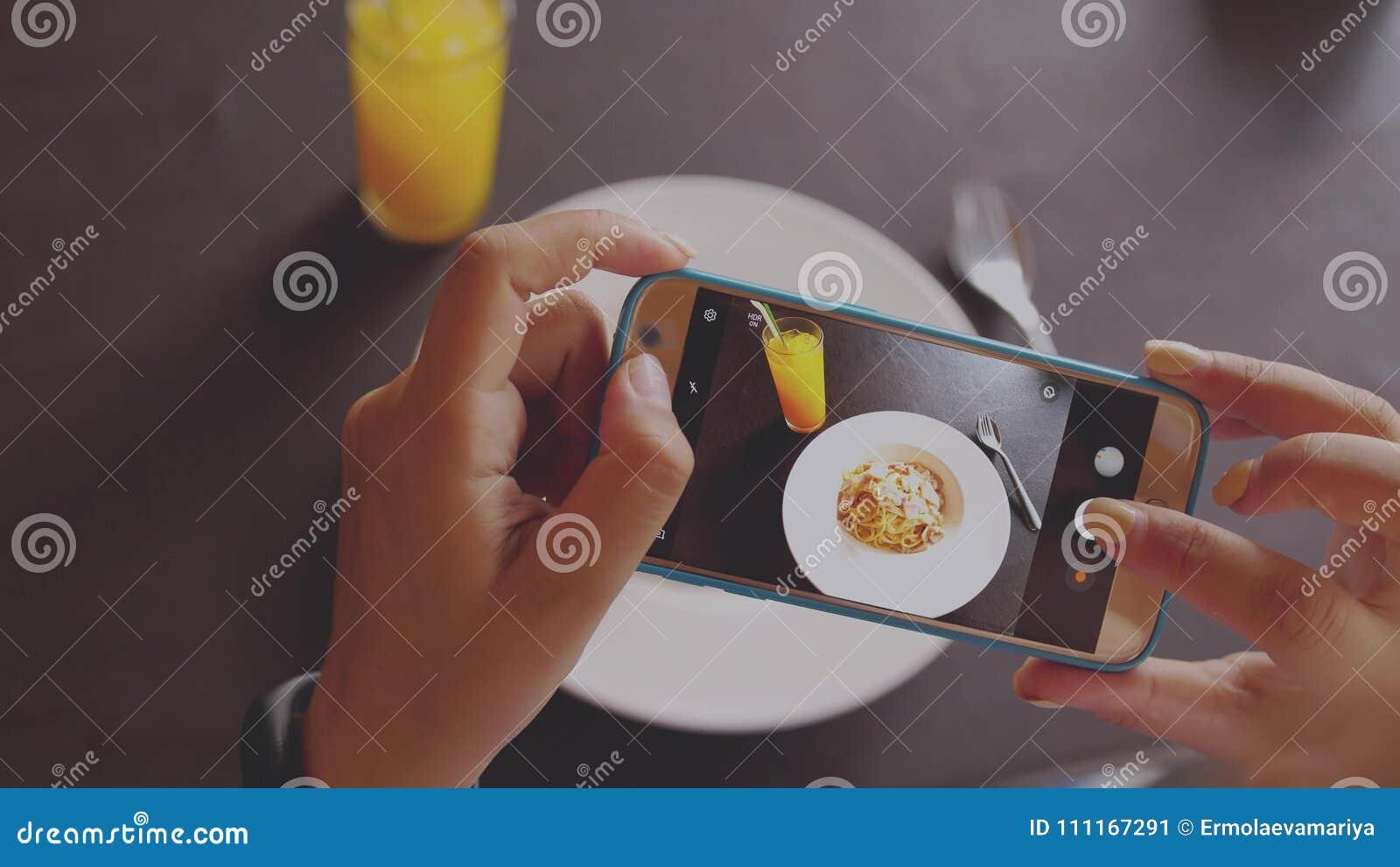 Main femelle prenant quelques photos de son mobile d un plat italien délicieux de nourriture Fin vers le haut