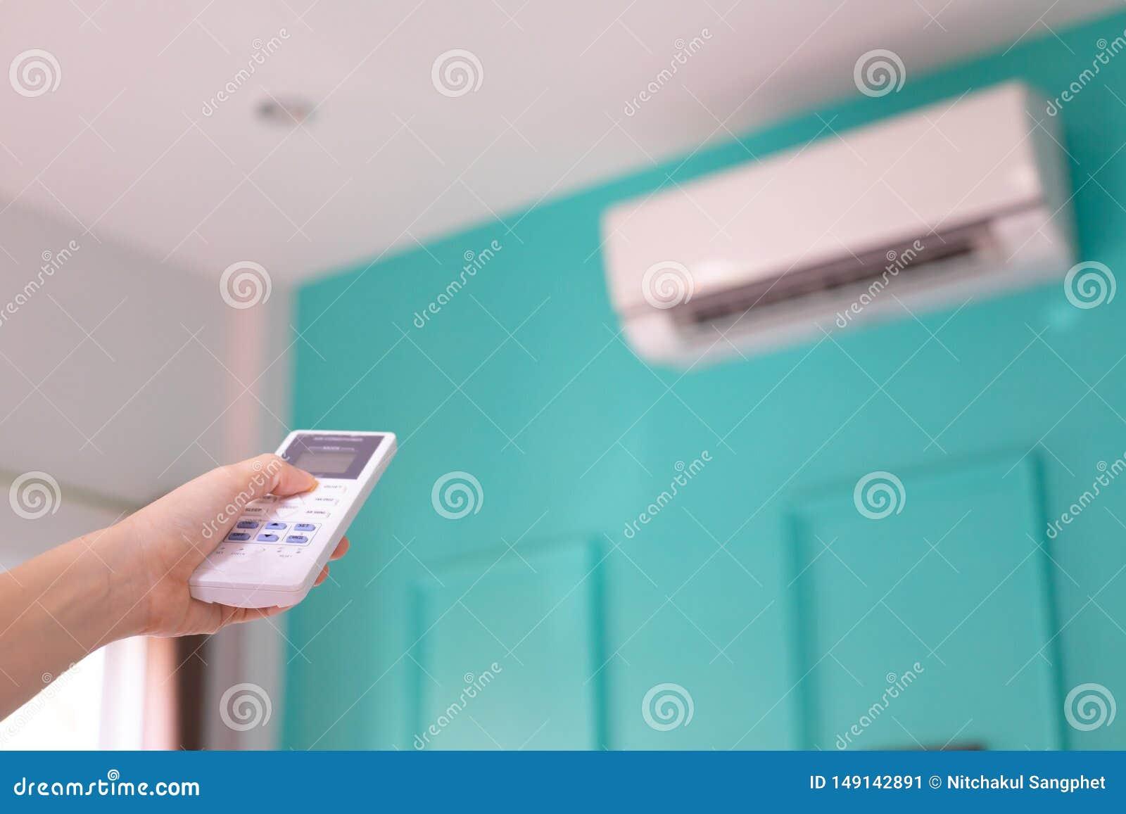 Main humaine pressant sur à télécommande pour le climatiseur de commutateur  MARCHE