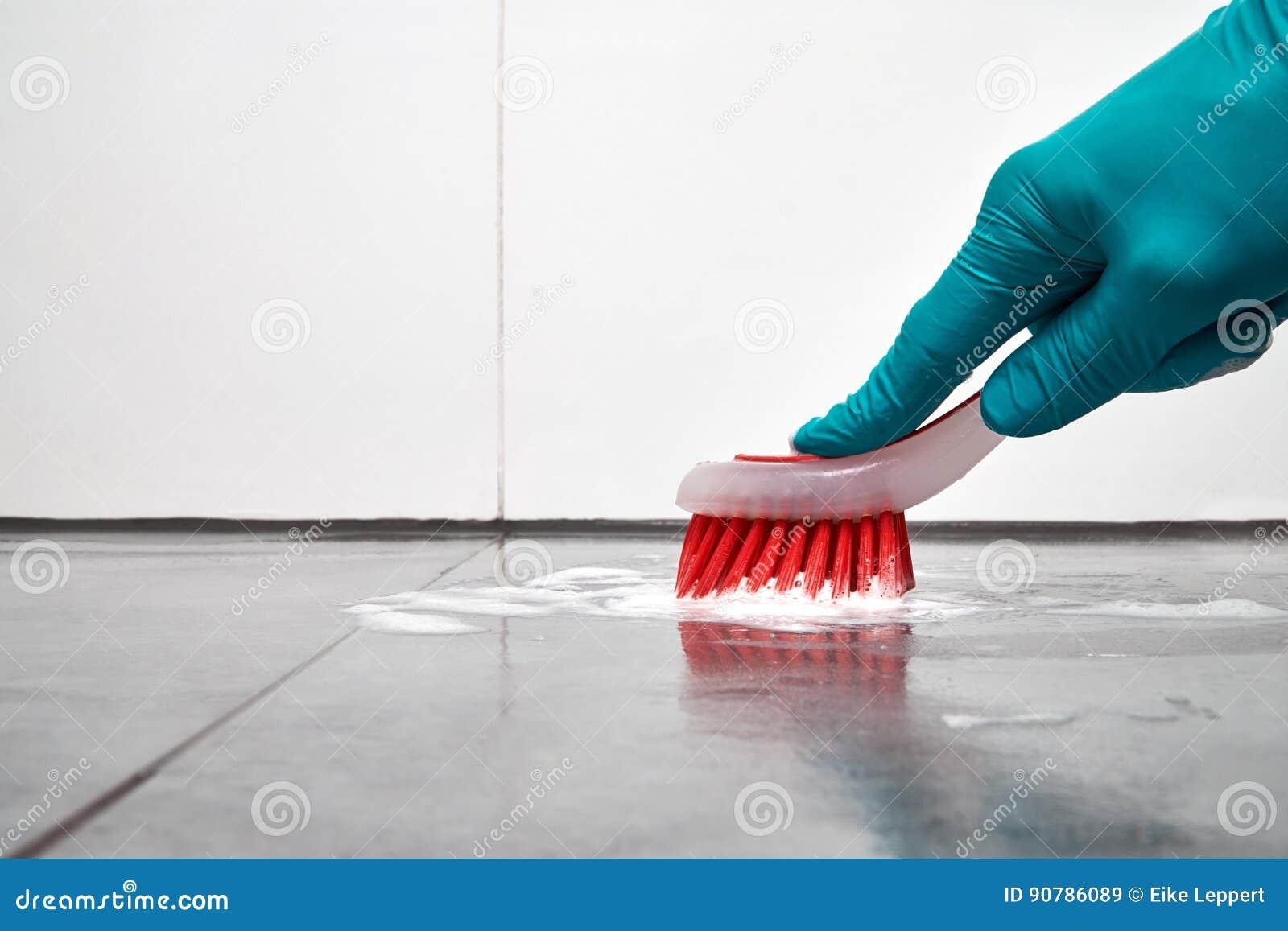 Main masculine avec le nettoyage de brosse rouge que la salle de bains couvre de tuiles sur le - Nettoyage de salle de bain ...