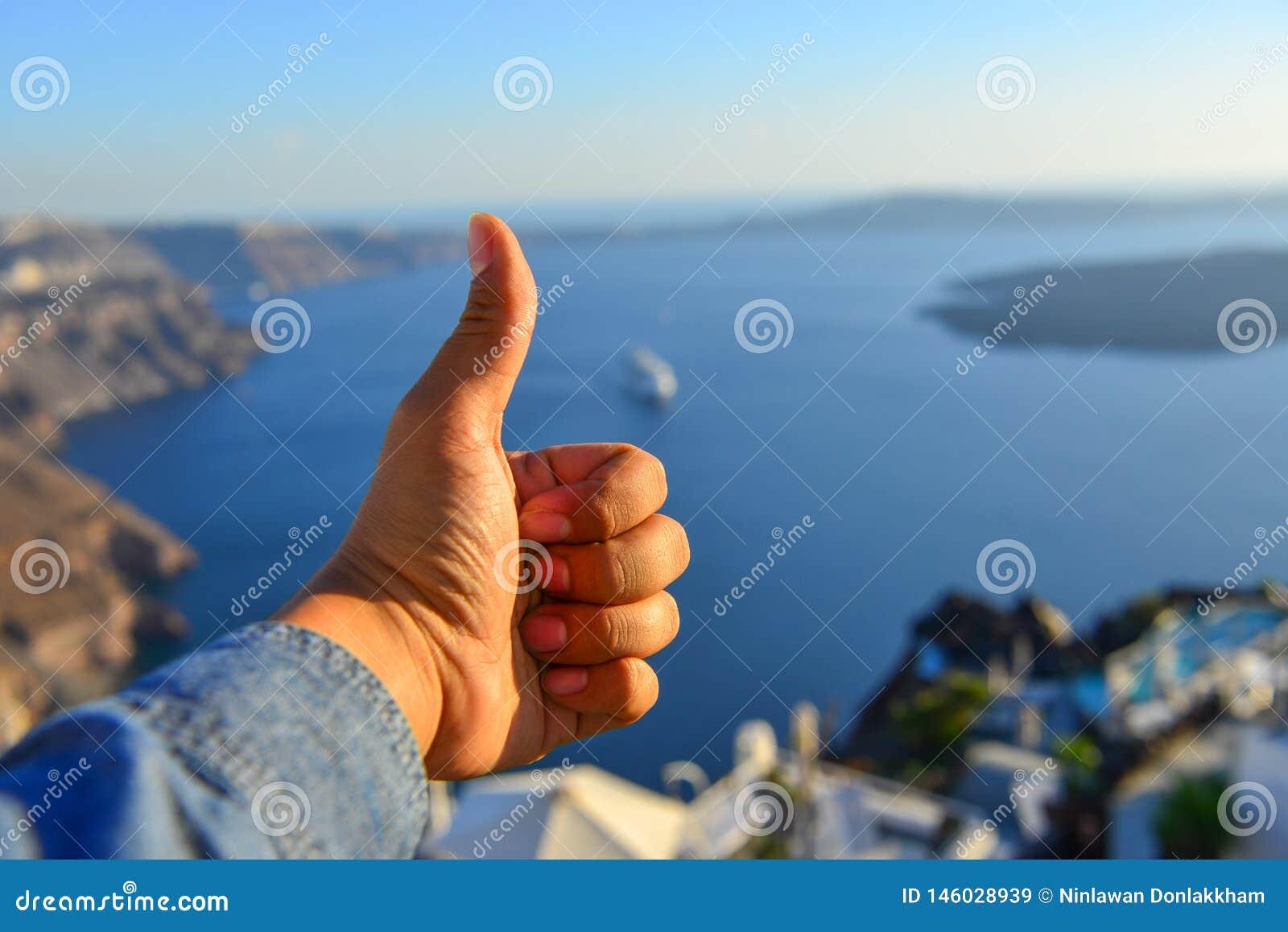 Main masculine avec le paysage marin de l ?le de Santorini