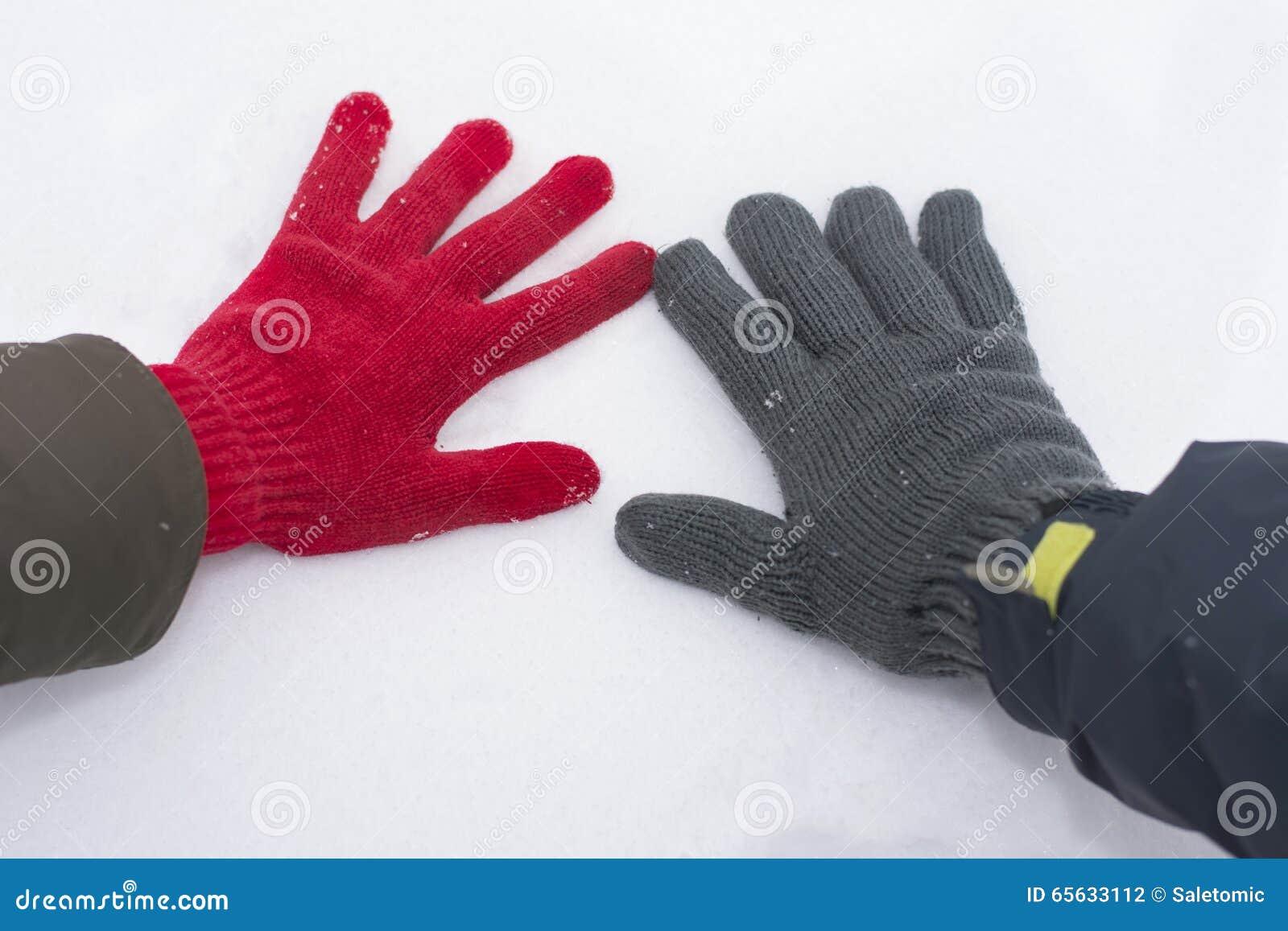 Main masculine et femelle dans les gants touchant la neige