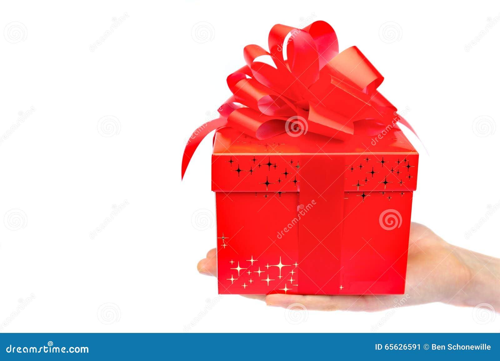 Main masculine présentant la boîte de Noël rouge sur la main plate