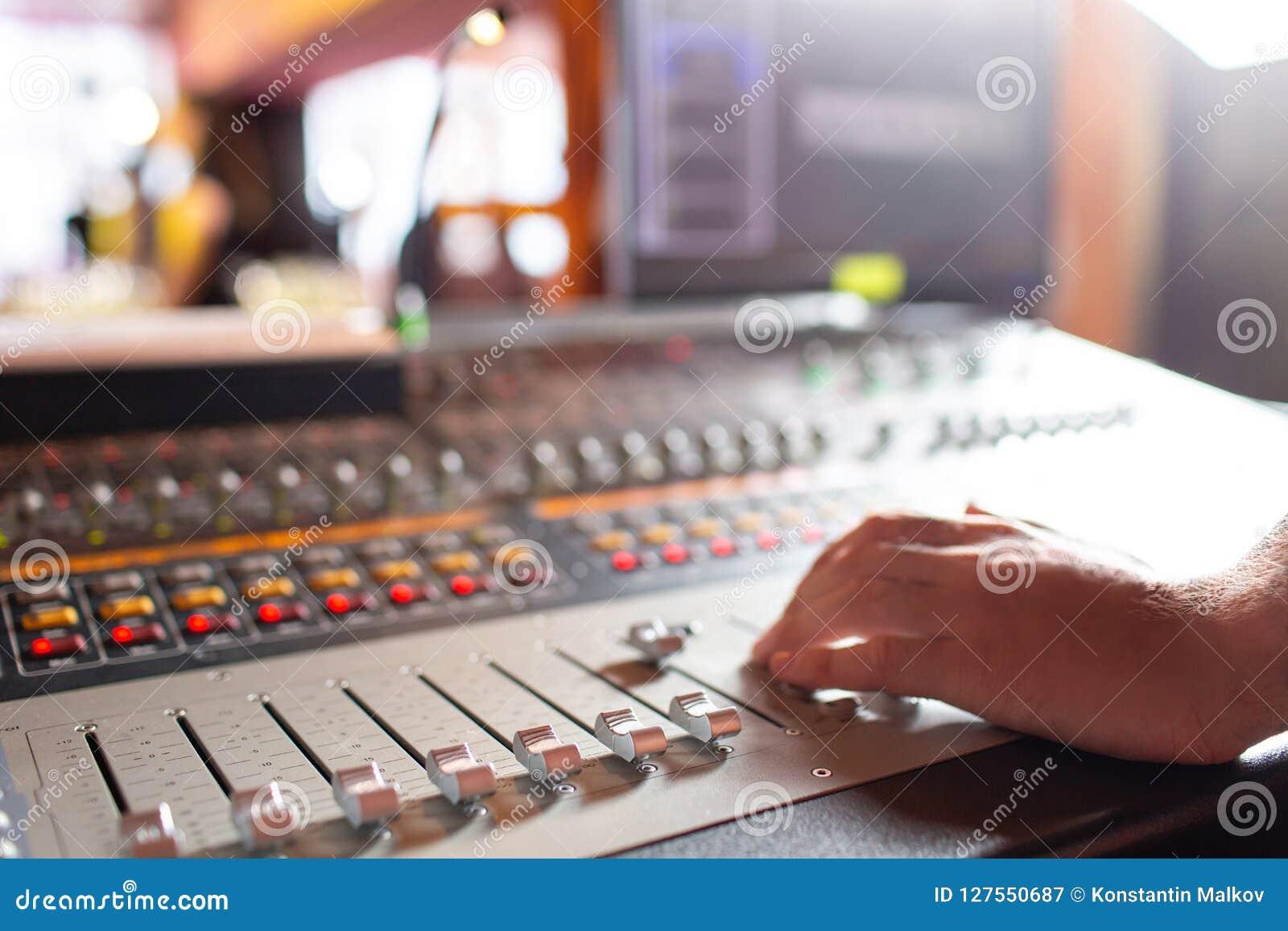 Main masculine sur l affaiblisseur de contrôle sur la console Bureau de mélange de studio d enregistrement sonore avec l ingénieu