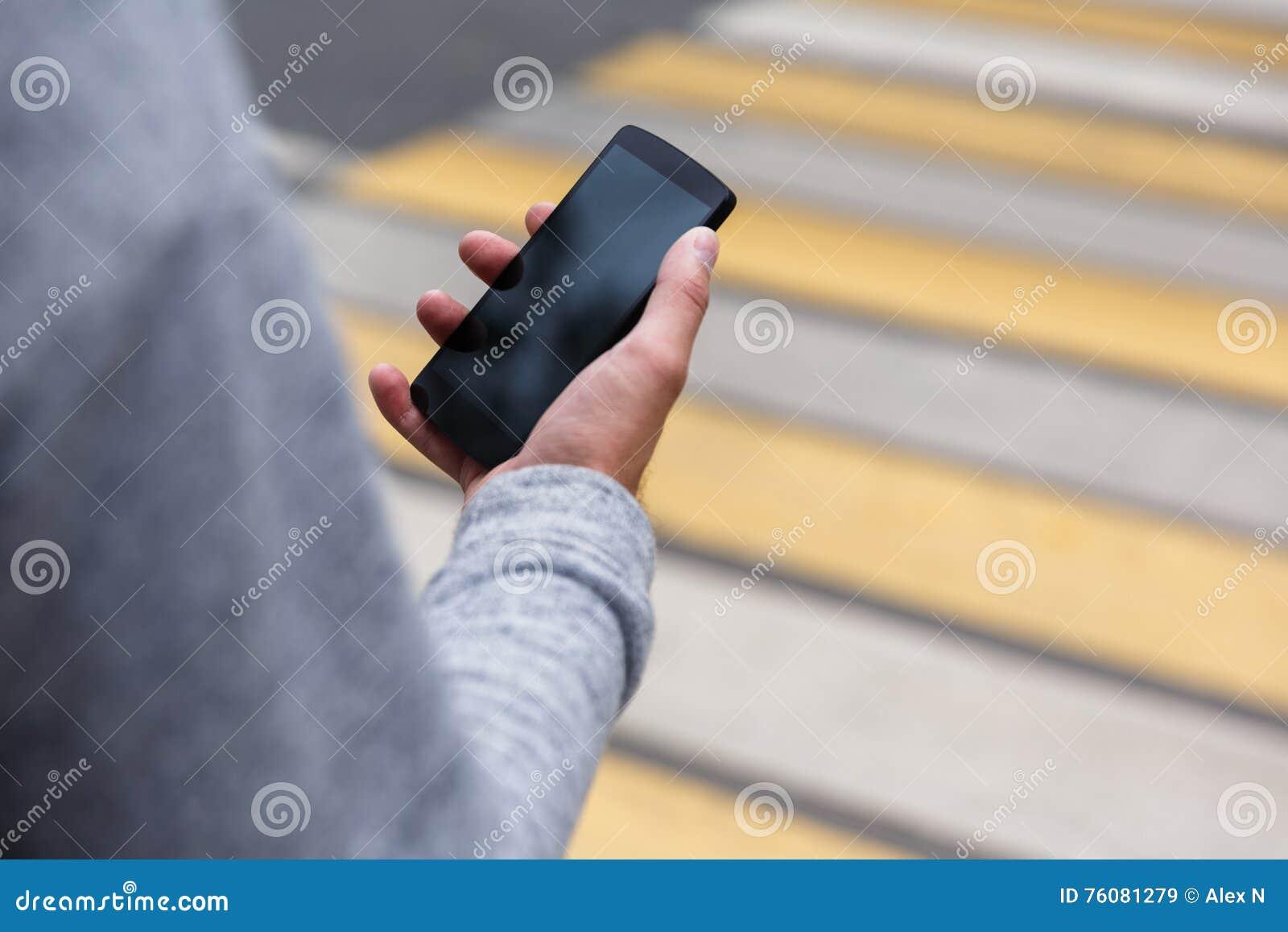 Main masculine tenant le smartphone avec l écran vide sur le passage pour piétons