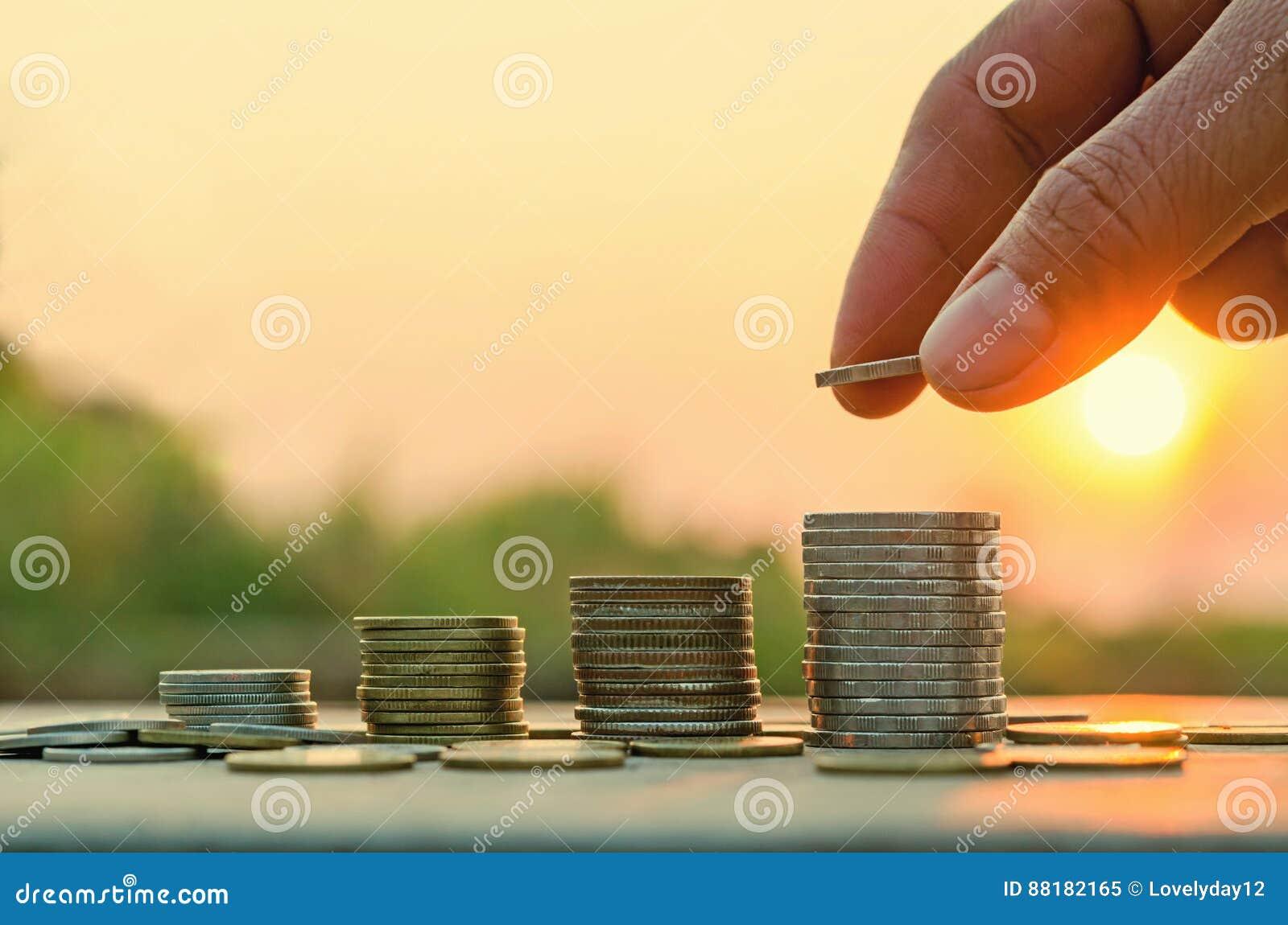 Main mettant la pièce de monnaie sur la pile de pièces de monnaie