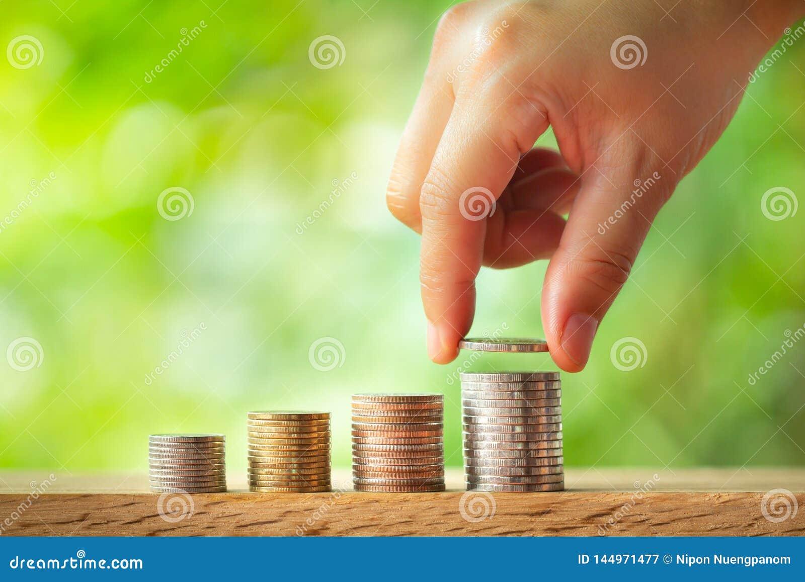 Main mettant la pi?ce de monnaie sur la pile de pi?ces de monnaie avec le fond brouill? par verdure