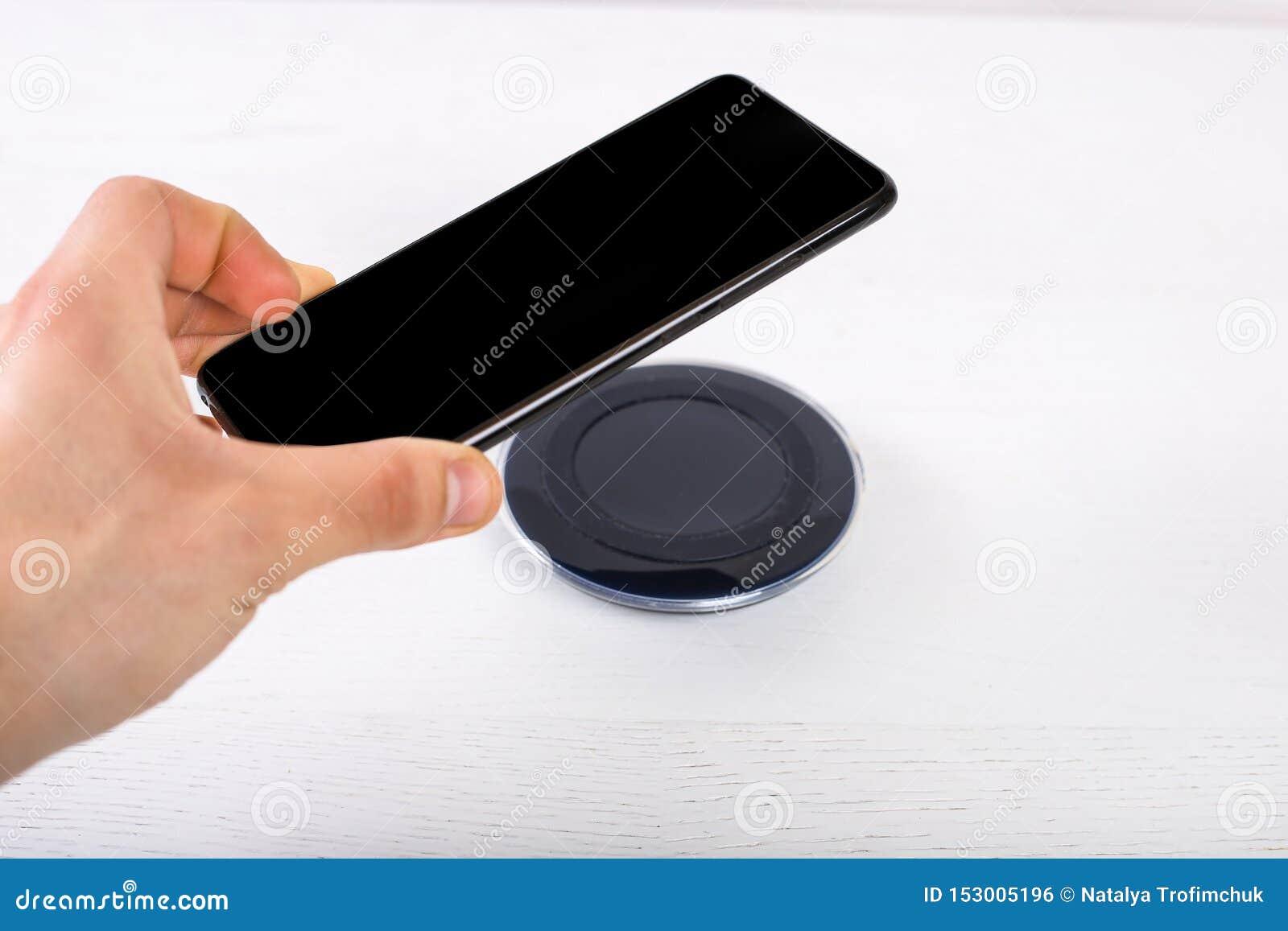 Main mettant le téléphone portable sur le chargeur sans fil, équipement moderne sur le fond blanc