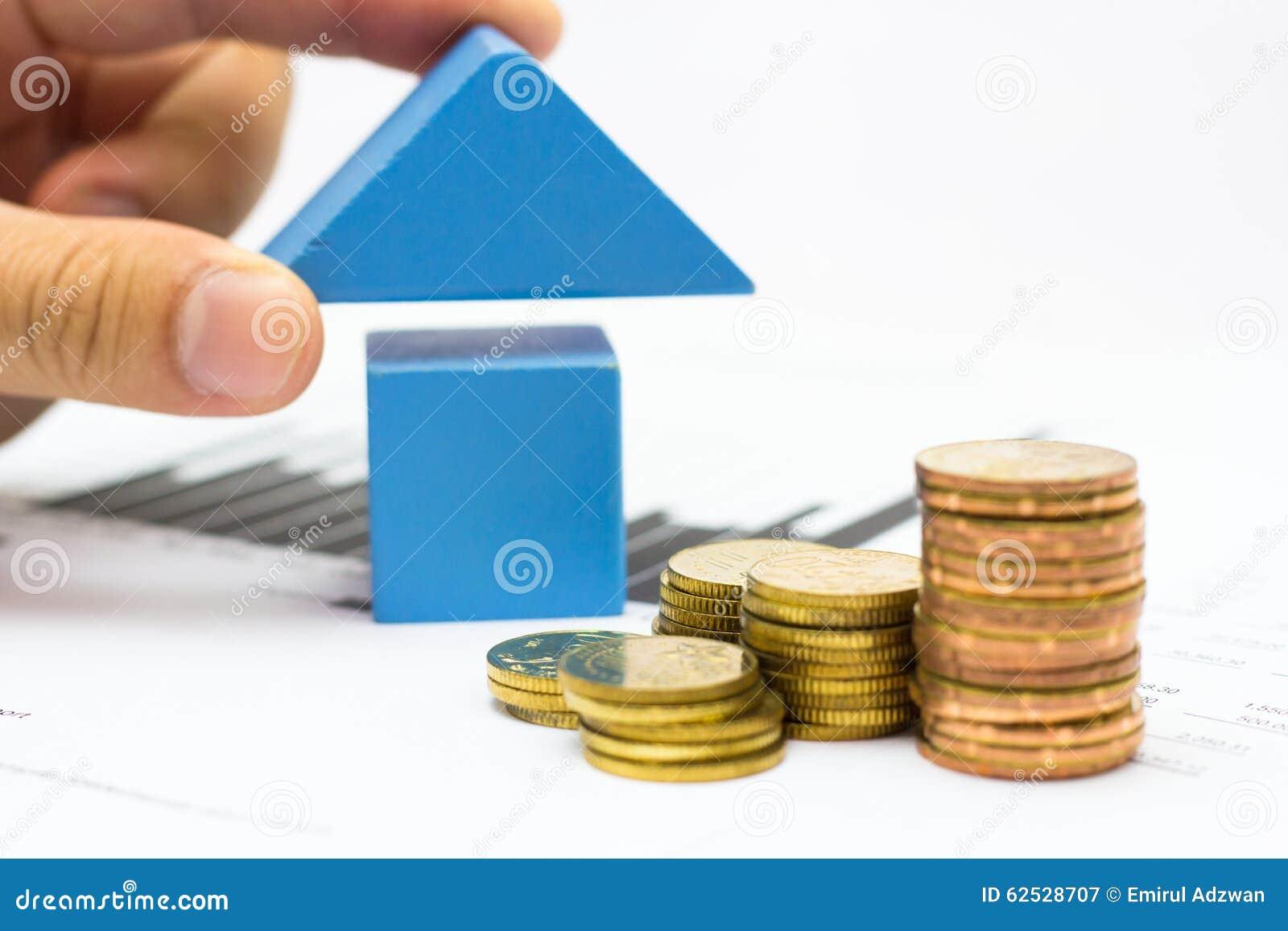 main mettant le toit pour le bloc en bois bleu de maison et le
