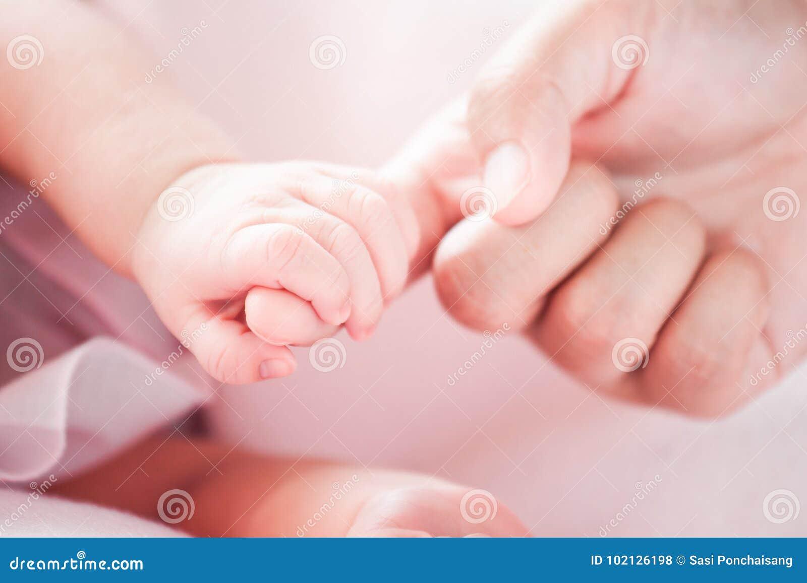 Main nouveau-née minuscule de bébé tenant le doigt de mère avec amour