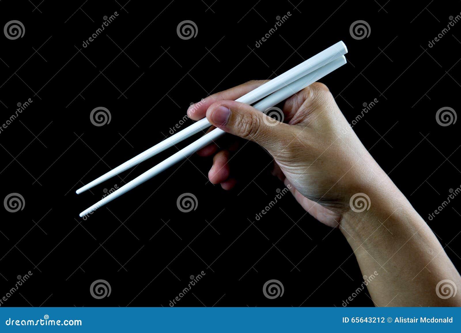 Main tenant des baguettes sur le fond noir
