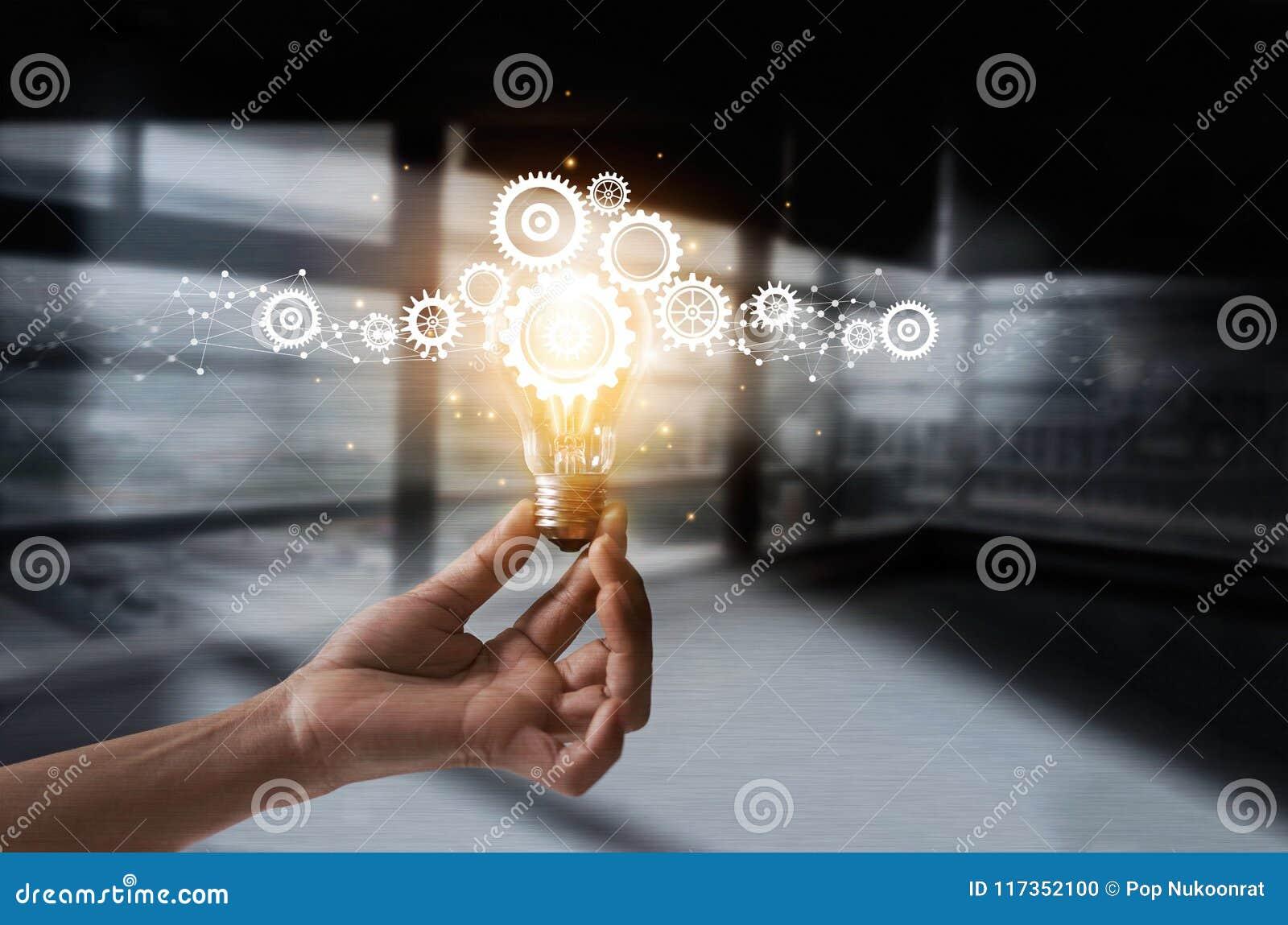 Main tenant l ampoule et la dent à l intérieur Idée et imagination