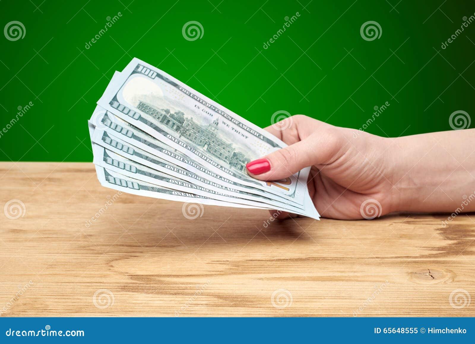 Main tenant l argent sur une table en bois