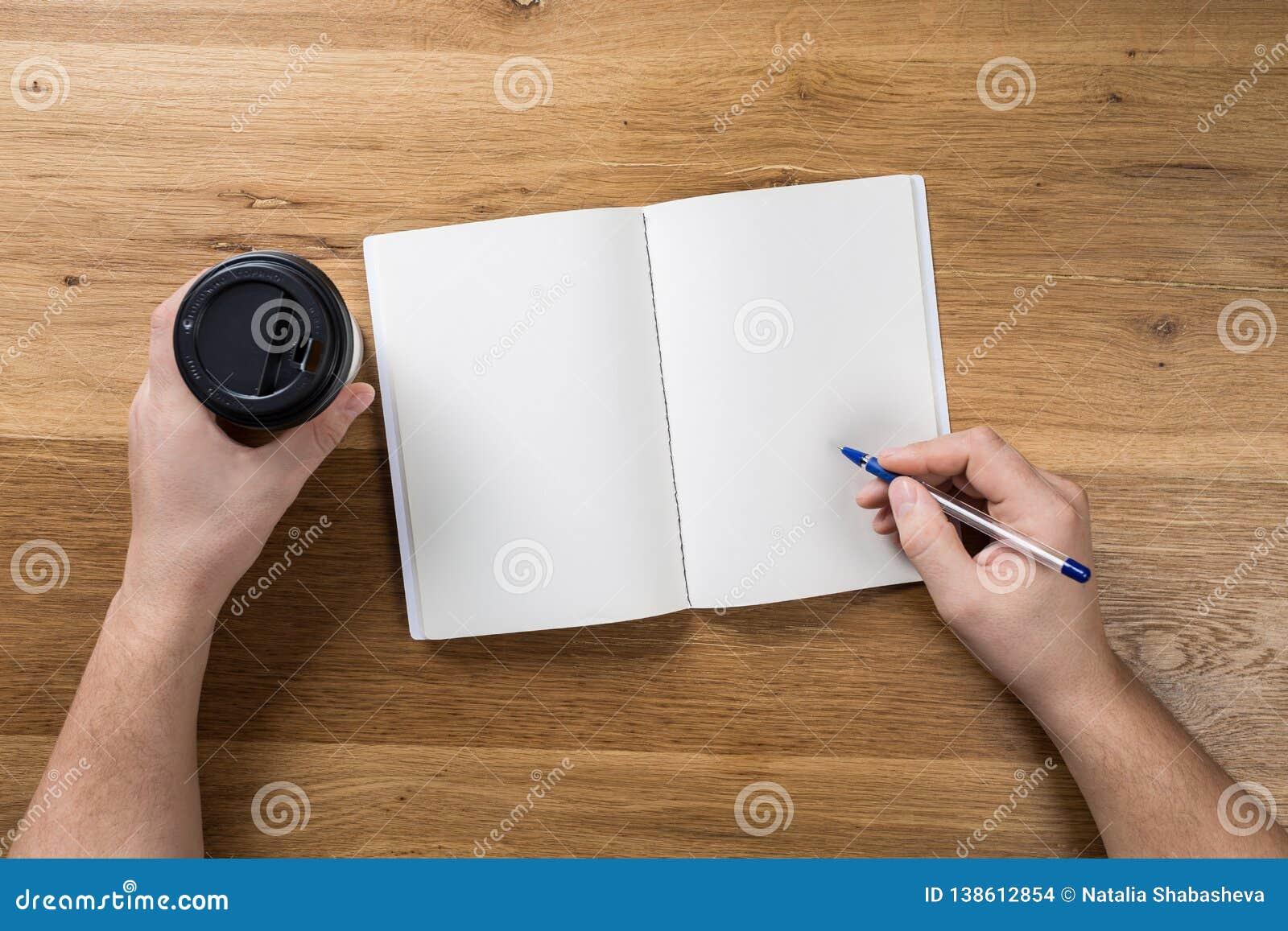 Main tenant la maquette blanche de feuille de papier blanc sur le fond en bois