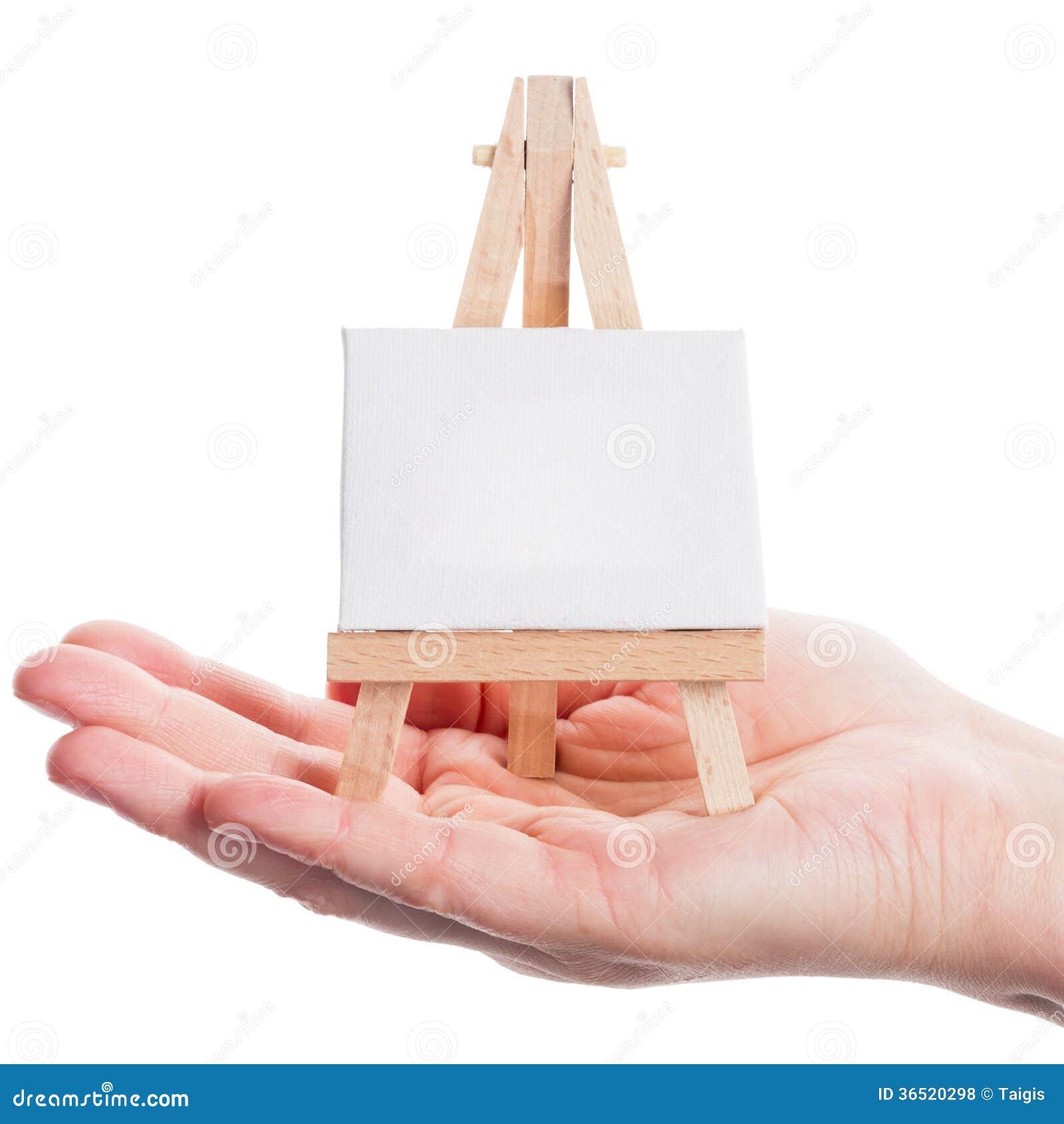 Main tenant le chevalet avec la toile