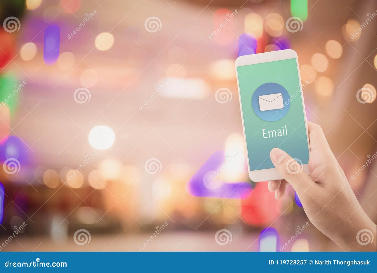 Main tenant le contrôle d homme et envoyant le message avec l email dans un téléphone sur le fond abstrait de bokeh