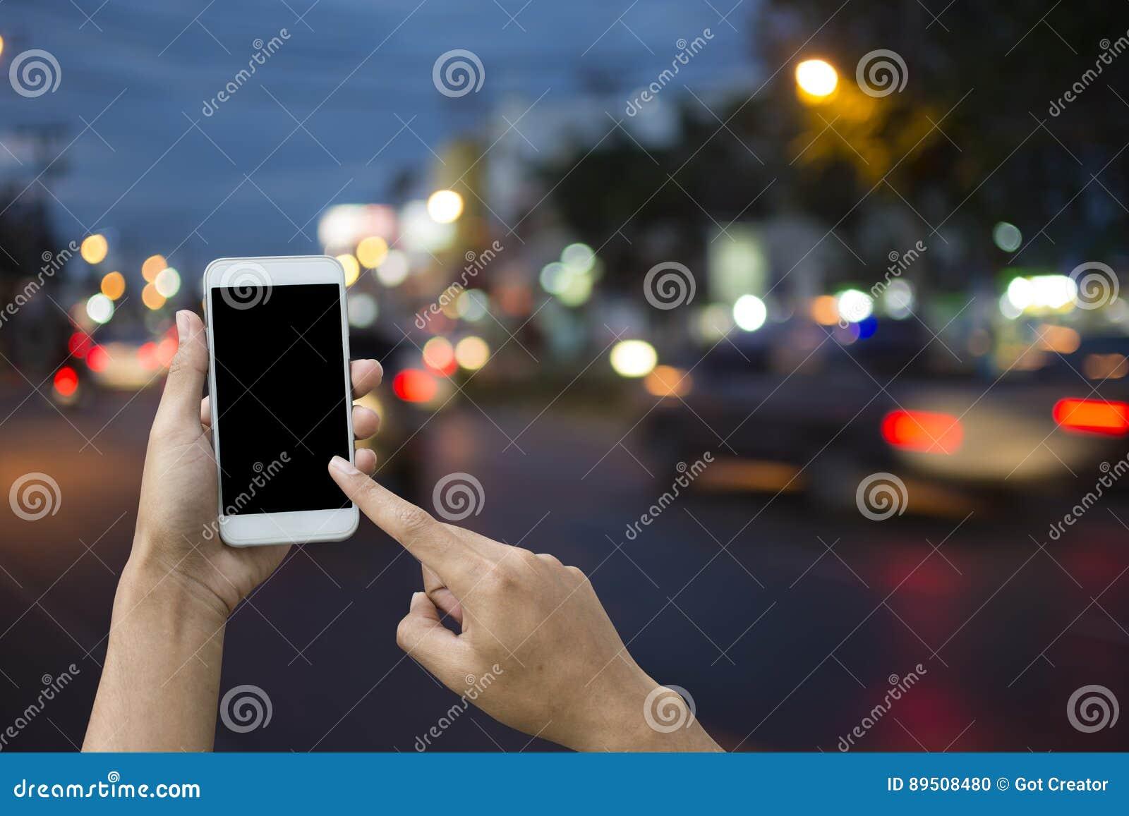 Main tenant le smartphone sur le transport de fond de tache floue